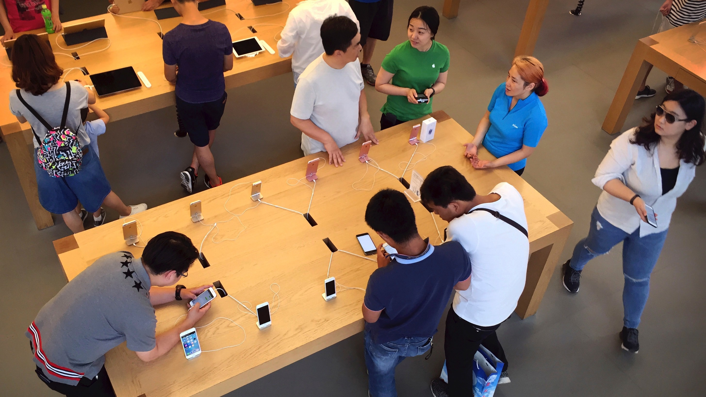 Customers look at Apple iPhone SE and 6S models on display at an Apple Store in Beijing, Saturday, June 18, 2016. A Chinese regulator has ordered Apple Inc. to stop selling two versions of its iPhone 6 in the city of Beijing after finding it looks too much like a competitor, but Apple says sales are going ahead while it appeals. (AP Photo/Mark Schiefelbein)