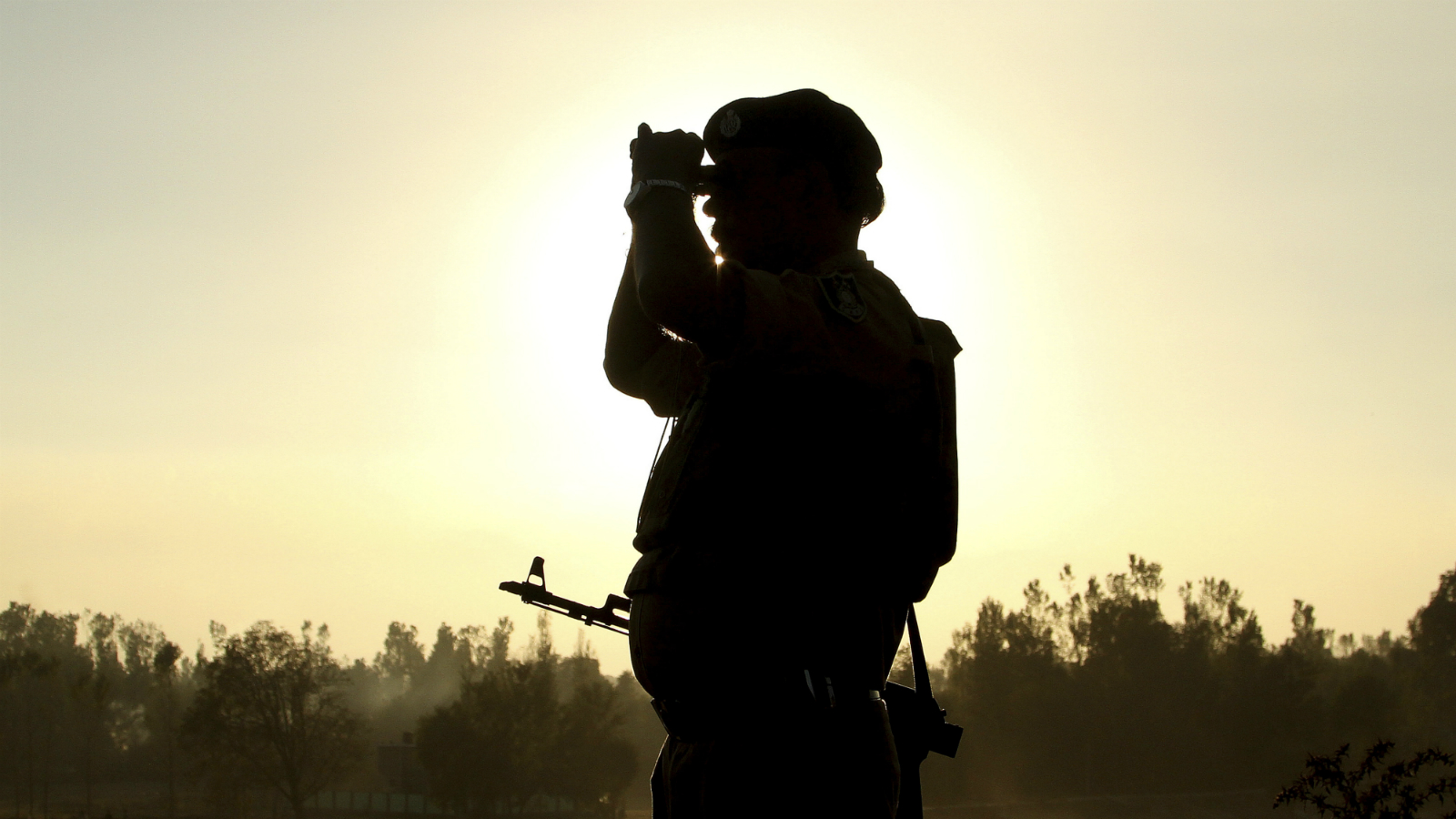 An Indian soldier looks through a binocular as he stands vigil near a building where suspected militants have taken refuge during a gun battle in Pampore, on the outskirts of Srinagar, Indian controlled Kashmir, Tuesday, Oct. 11, 2016. A handful of rebels holed up in a building in the Indian portion of Kashmir exchanged fire with government forces for the second straight day on Tuesday.