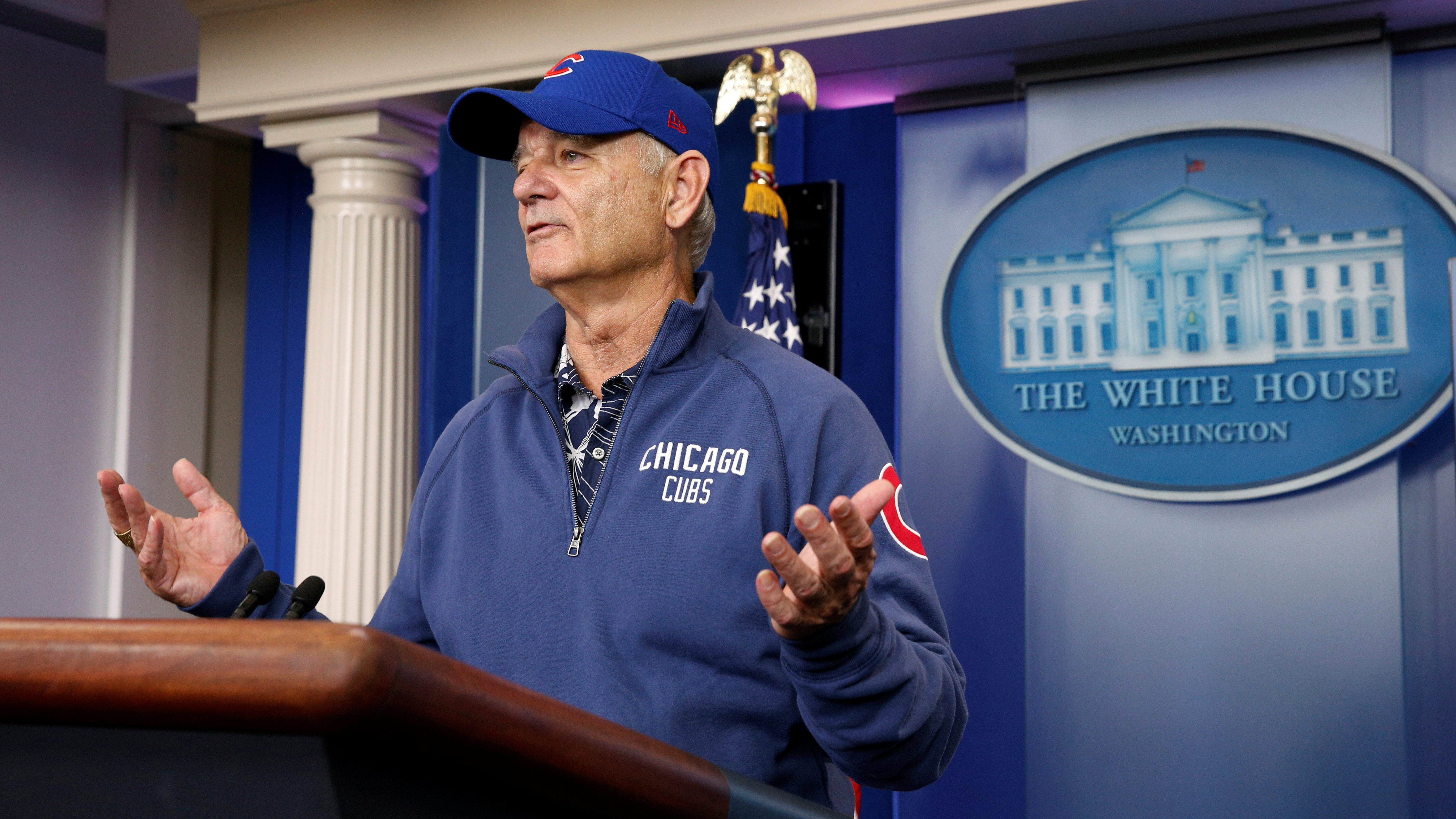 Actor Bill Murray, in Chicago Cubs attire, takes to the lectern in the briefing room during a visit to the White House.