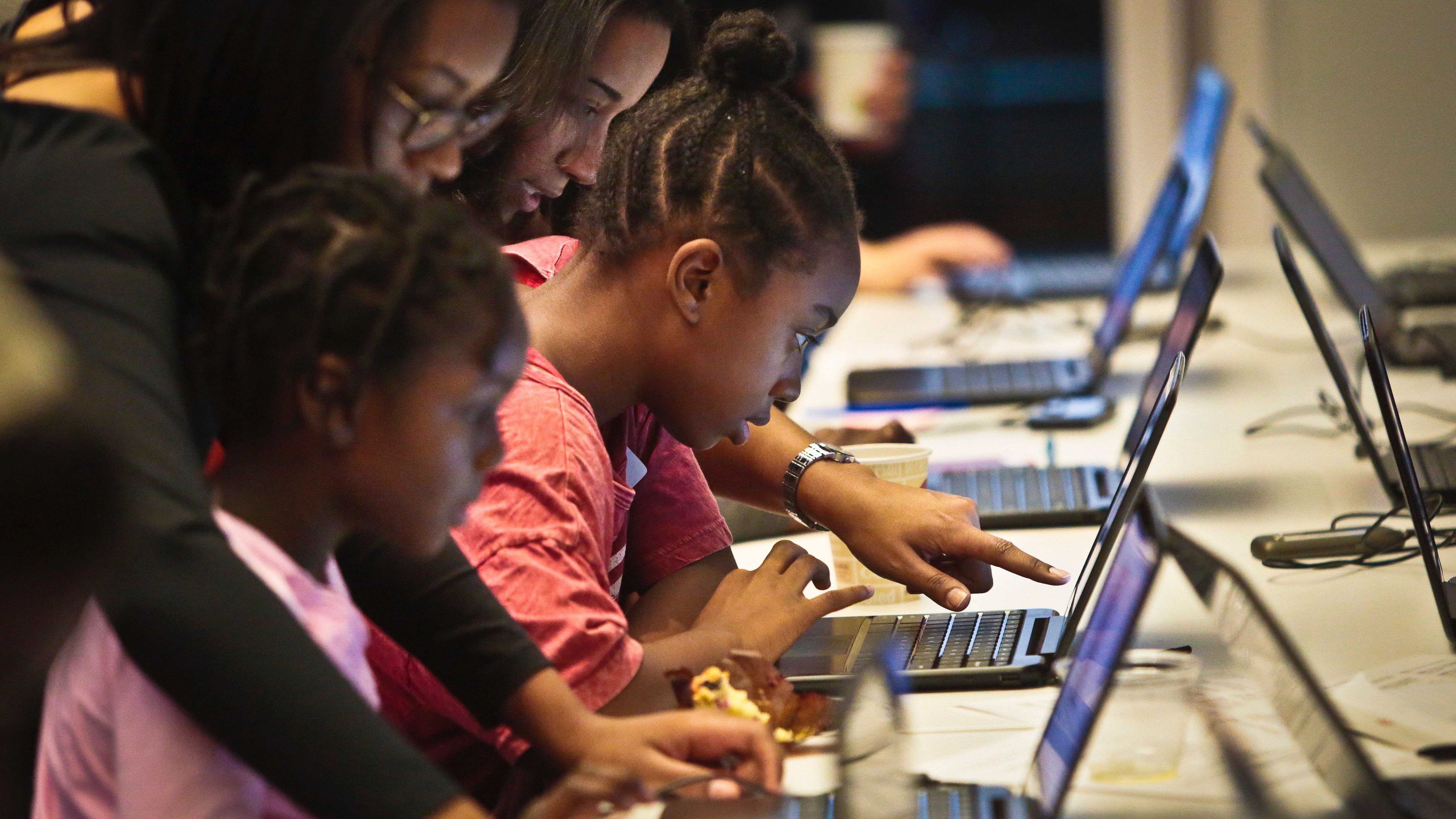 Black Girls Code (BGC) workshop volunteers Ashley Tolbert, second from left, and Nagita Sykes, second from right, guide sisters Jessica Ostrun, 11, far right, and Jayda Ostrun, 7, during an app building session at Google, on Saturday, Dec. 14, 2013 in New York.  BGC introduces basic programming to girls from a segment of the population now poorly represented in the high technology workforce. (AP Photo/Bebeto Matthews)