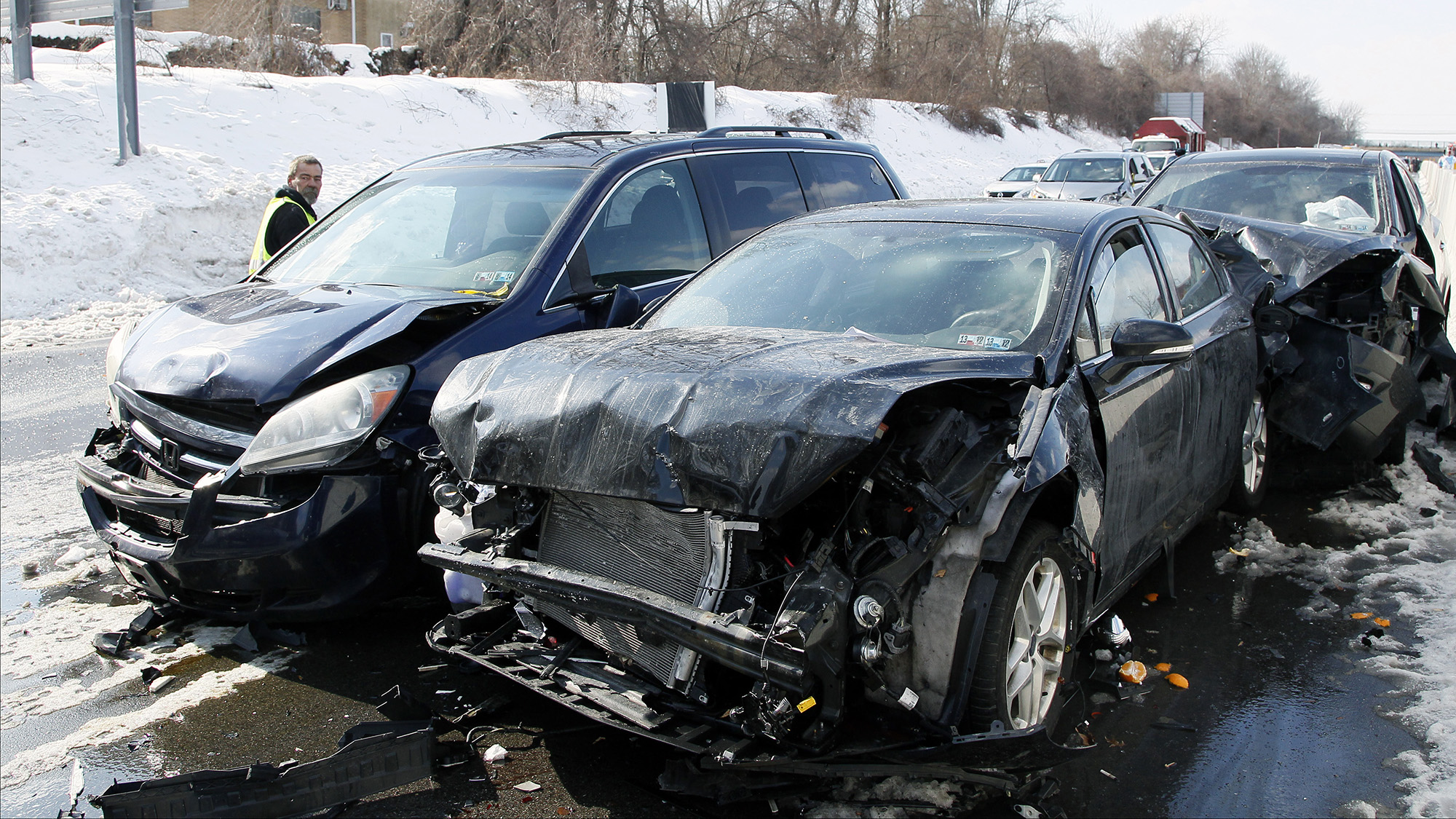 Smashed cars litter at the scene of an earlier multi-car and truck pile up the Pennsylvania Turnpike near the Bensalem interchange in Pennsylvania, February 14, 2014. The Pennsylvania Turnpike was littered with twisted metal from up to 50 vehicles in multiple accidents that injured at least 30 people. The road had to be closed during the morning commute, causing a 7-mile (11-km) backup, said Renee Vid Colborn, a spokeswoman for the Pennsylvania Turnpike Commission.   REUTERS/Tom Mihalek (UNITED STATES - Tags: DISASTER ENVIRONMENT) - RTX18UH4