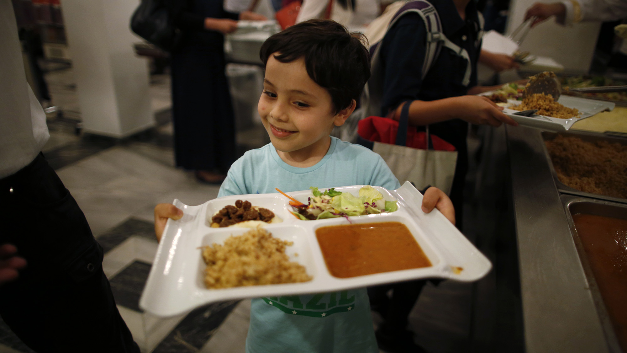 A Muslim boy residing in Japan has his iftar, breaking of fast meal, during the holy month of Ramadan at Tokyo Camii mosque in Tokyo June 29, 2014. REUTERS/Issei Kato (JAPAN - Tags: RELIGION FOOD) - RTR3WAF5