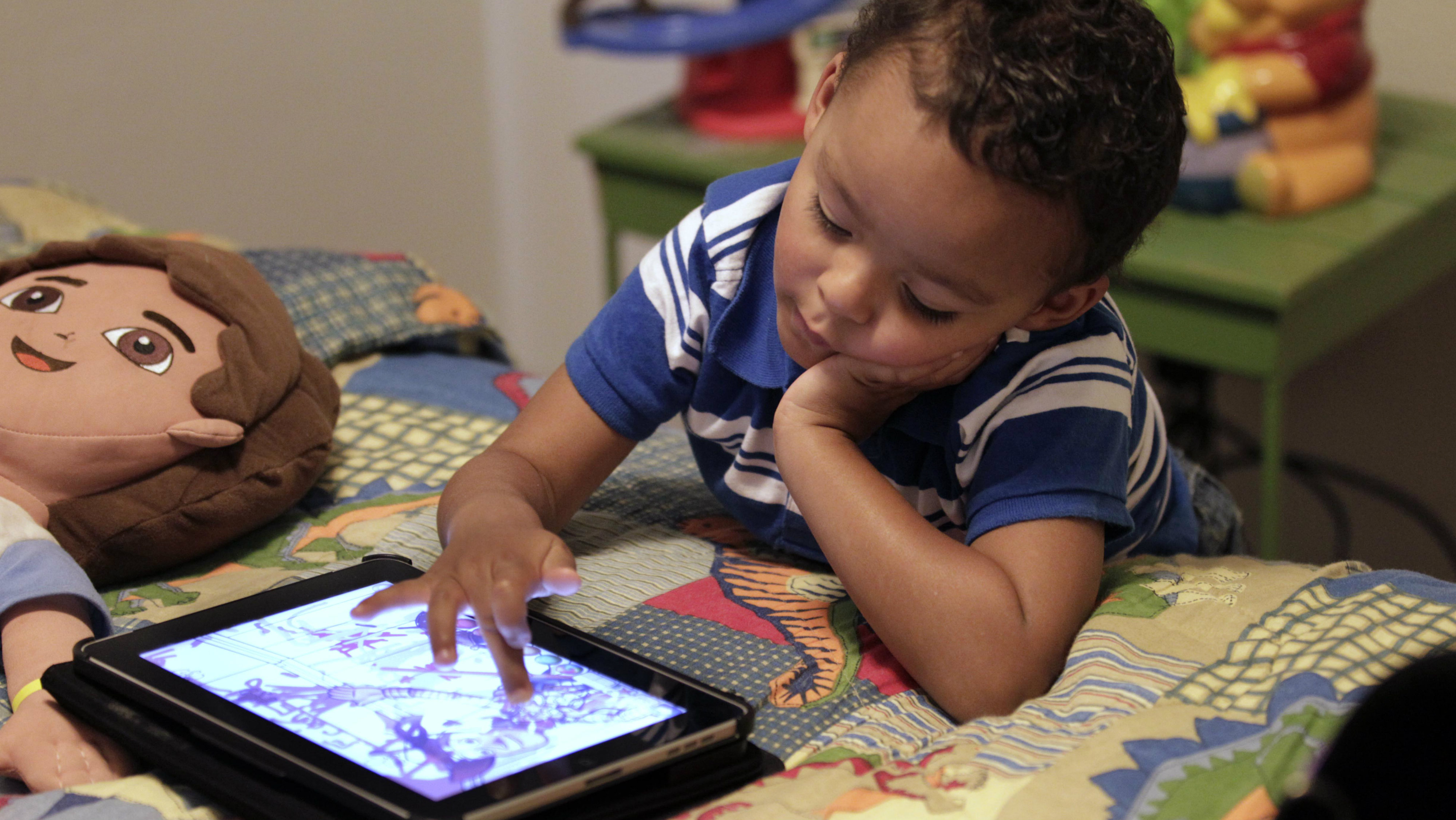 In this Friday, Oct. 21, 2011 file photo, Frankie Thevenot, 3, plays with an iPad in his bedroom at his home in Metairie, La. As of Wednesday, Aug. 7, 2013, the Campaign for a Commercial-Free Childhood, a Boston-based group, is urging federal investigators to examine the marketing practices of Fisher-Price's and Open Solution's mobile apps.