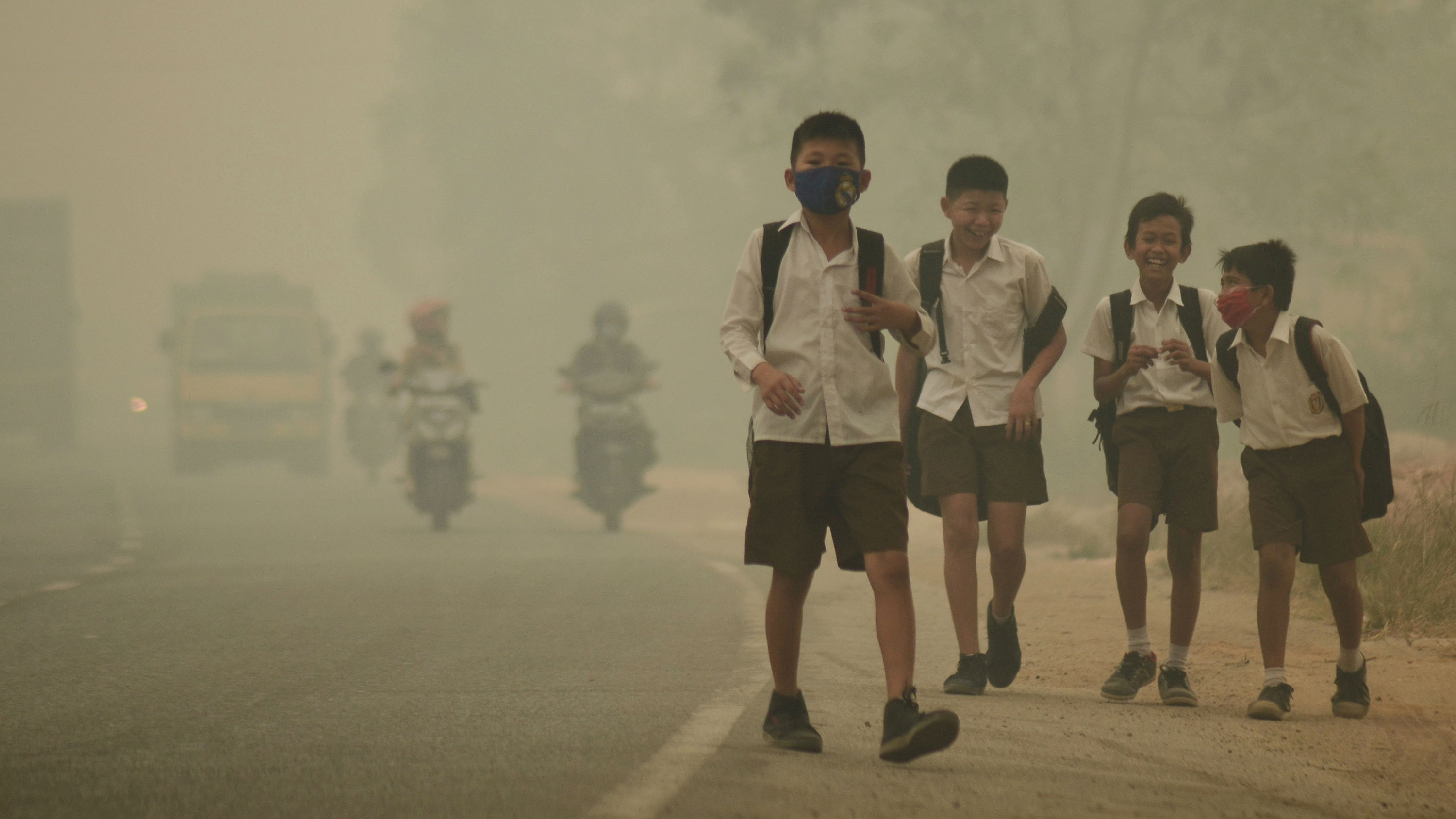 Four children walking along the side of the road with very smoggy air. Two have breathing masks on.