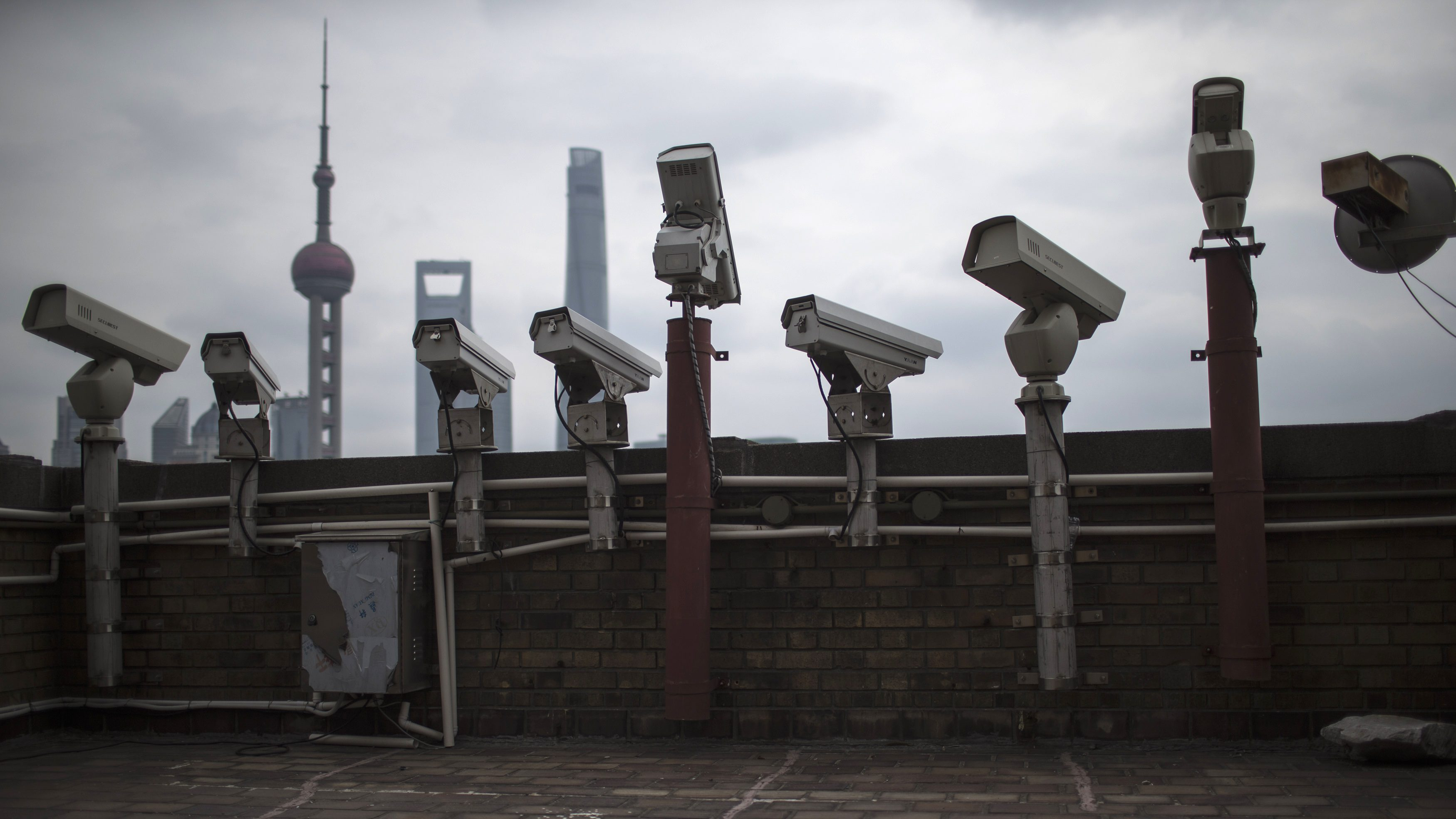 Security cameras are seen on a building at the Bund in front of the financial district of Pudong in Shanghai March 6, 2015. China's 2015 economic growth will meet the official target of around 7 percent, even though the economy faces headwinds, a senior government official said on Thursday.