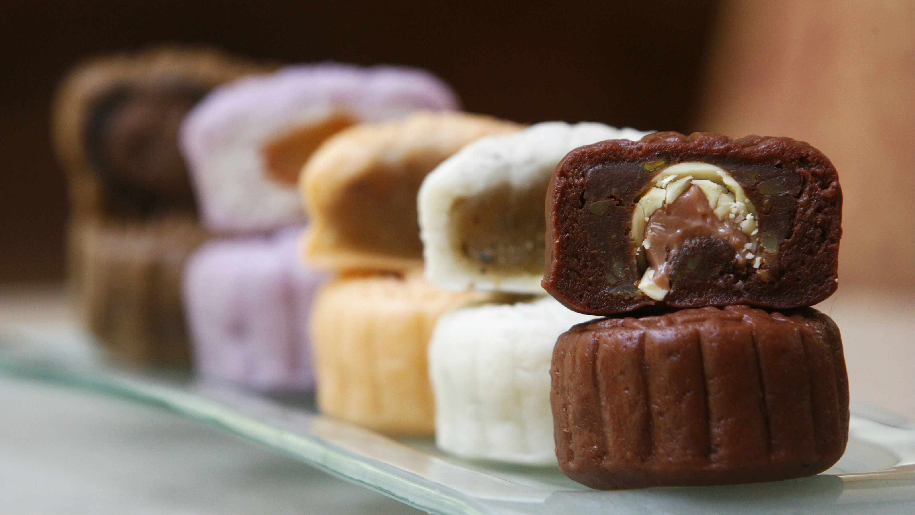 A variety of mooncakes with different fillings are displayed for the camera at a hotel in Singapore September 13, 2007. Ethnic Chinese families in Singapore usually give boxes of mooncakes to their families, friends and business contacts around the time of the mid-Autumn festival. Mooncakes displayed here are (front to back) Black Forest, Sweet Osmanther, Orange, Yam and Chocolate.