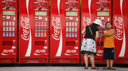 A woman and boy stand near Coca-Cola vending machines on the Olympic Green at the 2008 Beijing Olympics in Beijing on Saturday, Aug. 9, 2008. Coca-Cola, the world's biggest beverage company, moved to expand its operations in the fast-growing Chinese market Wednesday with a $2.5 billion bid for major juice maker China Huiyuan Juice Group Ltd.