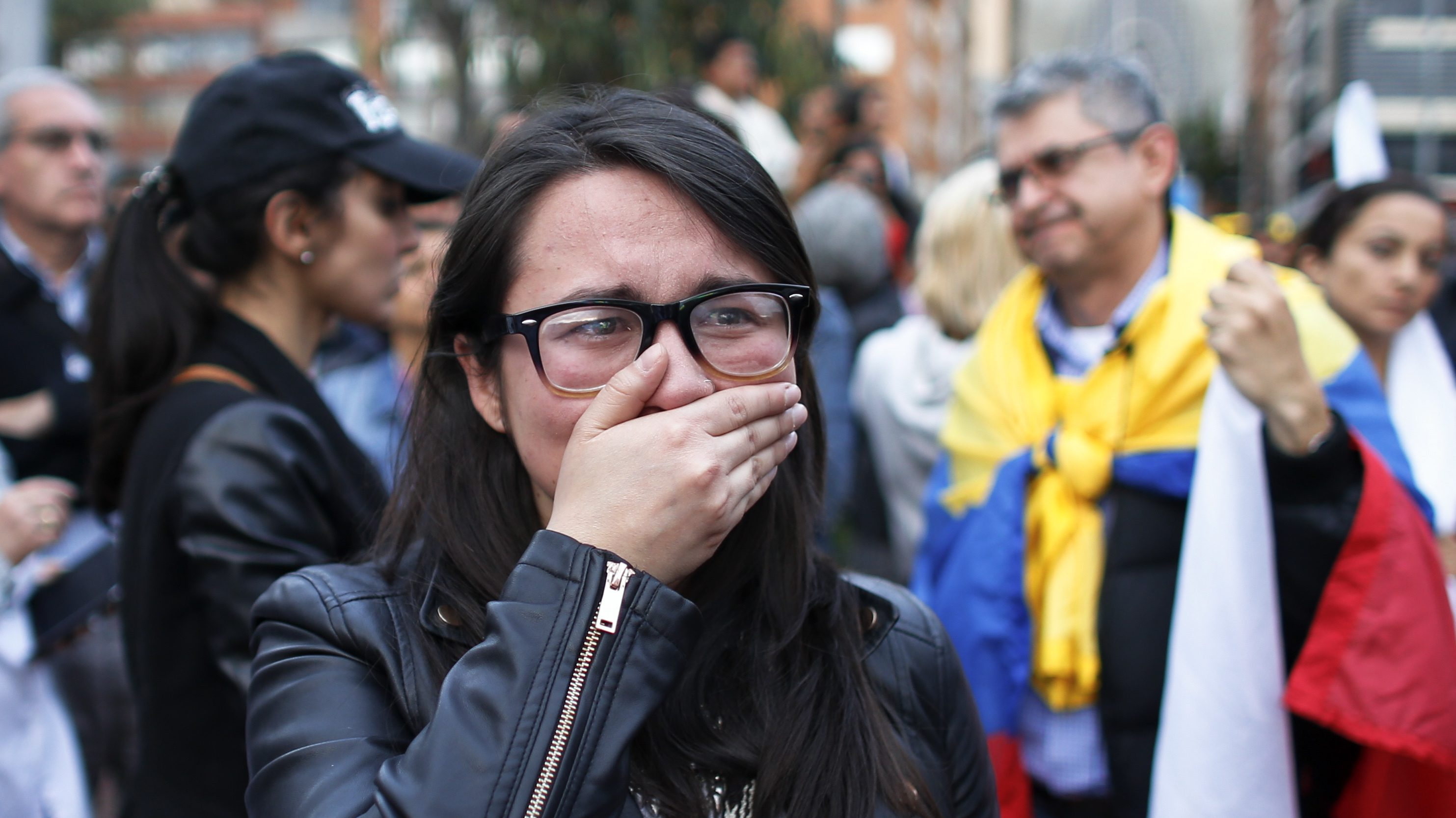 A supporters of the peace accord signed between the Colombian government and rebels of the Revolutionary Armed Forces of Colombia, FARC, cries as she follows on a giant screen the results of a referendum to decide whether or not to support the deal  in Bogota, Colombia, Sunday, Oct. 2, 2016.  Colombia's peace deal with leftist rebels was on the verge of collapsing in a national referendum Sunday, with those opposing the deal leading by a razor-thin margin with almost all votes counted. (AP Photo/Ariana Cubillos)