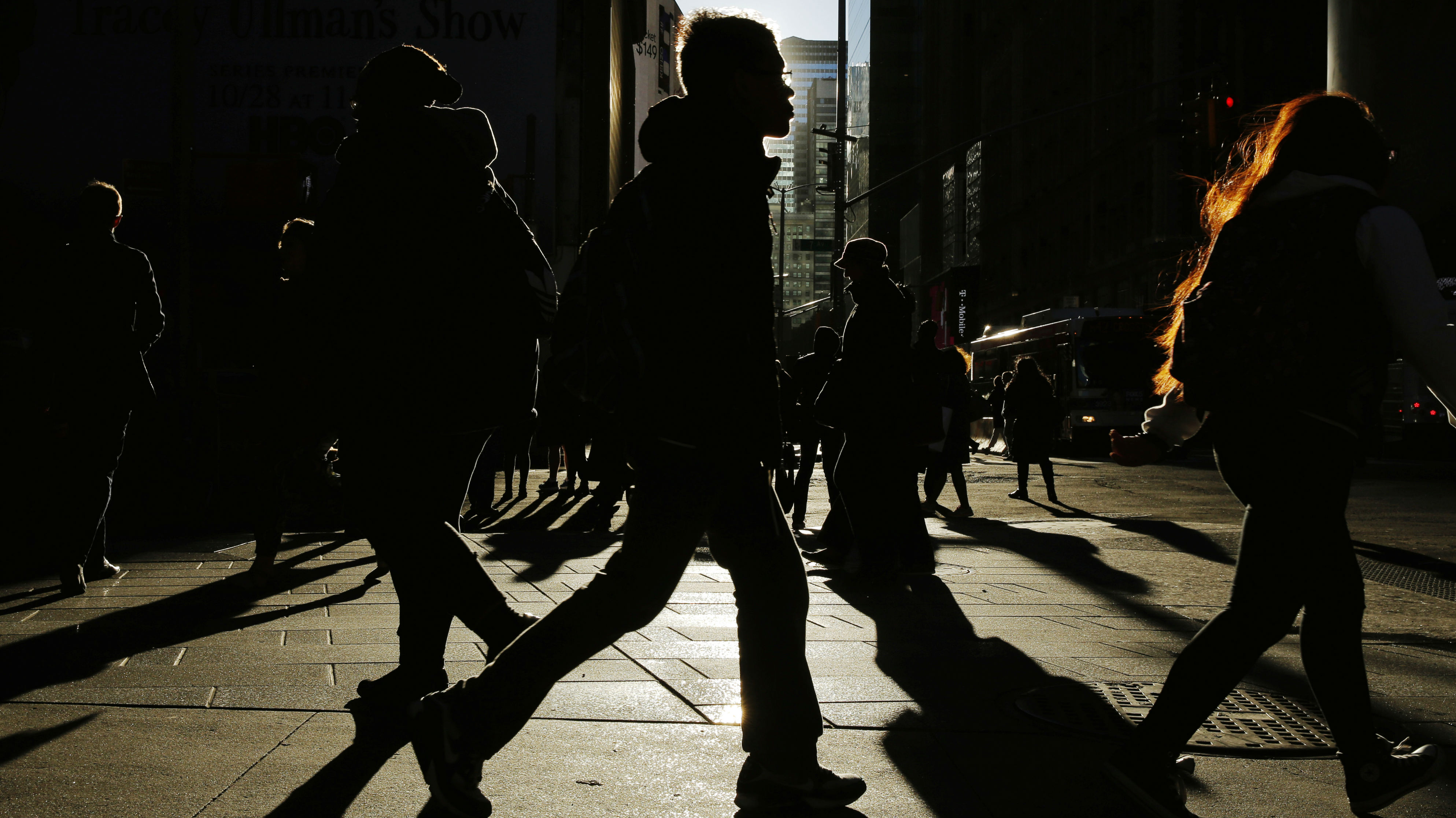Commuters walk through the early morning sun in New York, U.S.,October 31, 2016
