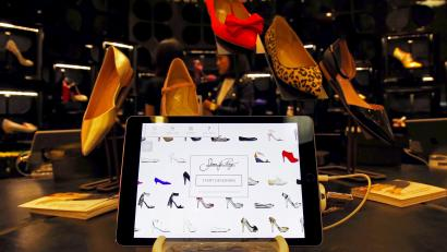 A tablet displays the Shoes of Prey website as Carmen Dang, a design consultant, stands next to designs being showcased in a large department store in central Sydney, Australia, October 1, 2015. Jodie Fox, a co-founder of Australian online retailer Shoes of Prey, which allows customers to design their own footwear, hopes to one day allow customers to print out pairs at home as technology improves and consumer demand grows for personalised products. Founded in 2009, Shoes of Prey allows women to create unique designs on its website, choosing from 300,000 trillion possible permutations of materials, colours, styles and sizes. It promises to deliver in four weeks but often manages two.