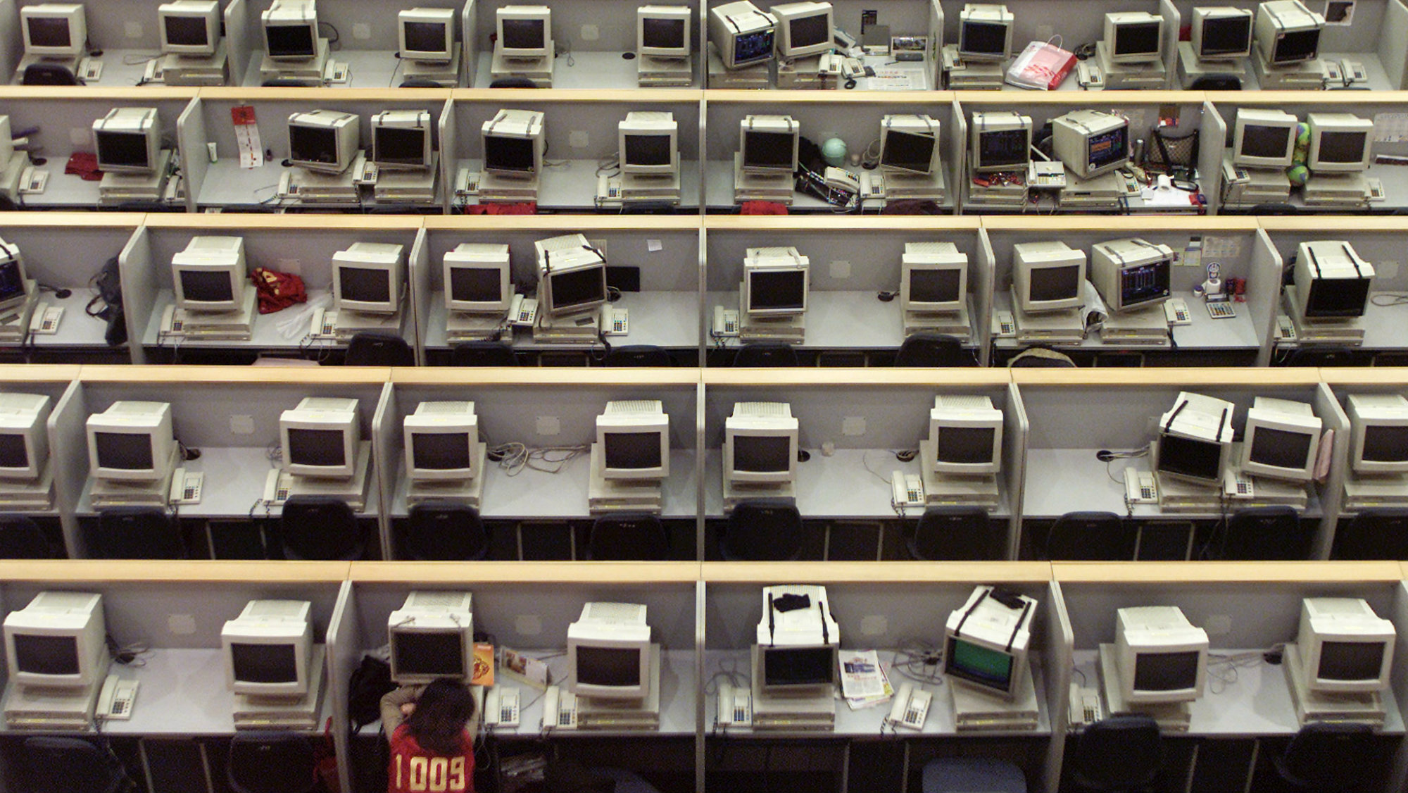 One person naps at a bank of old computers