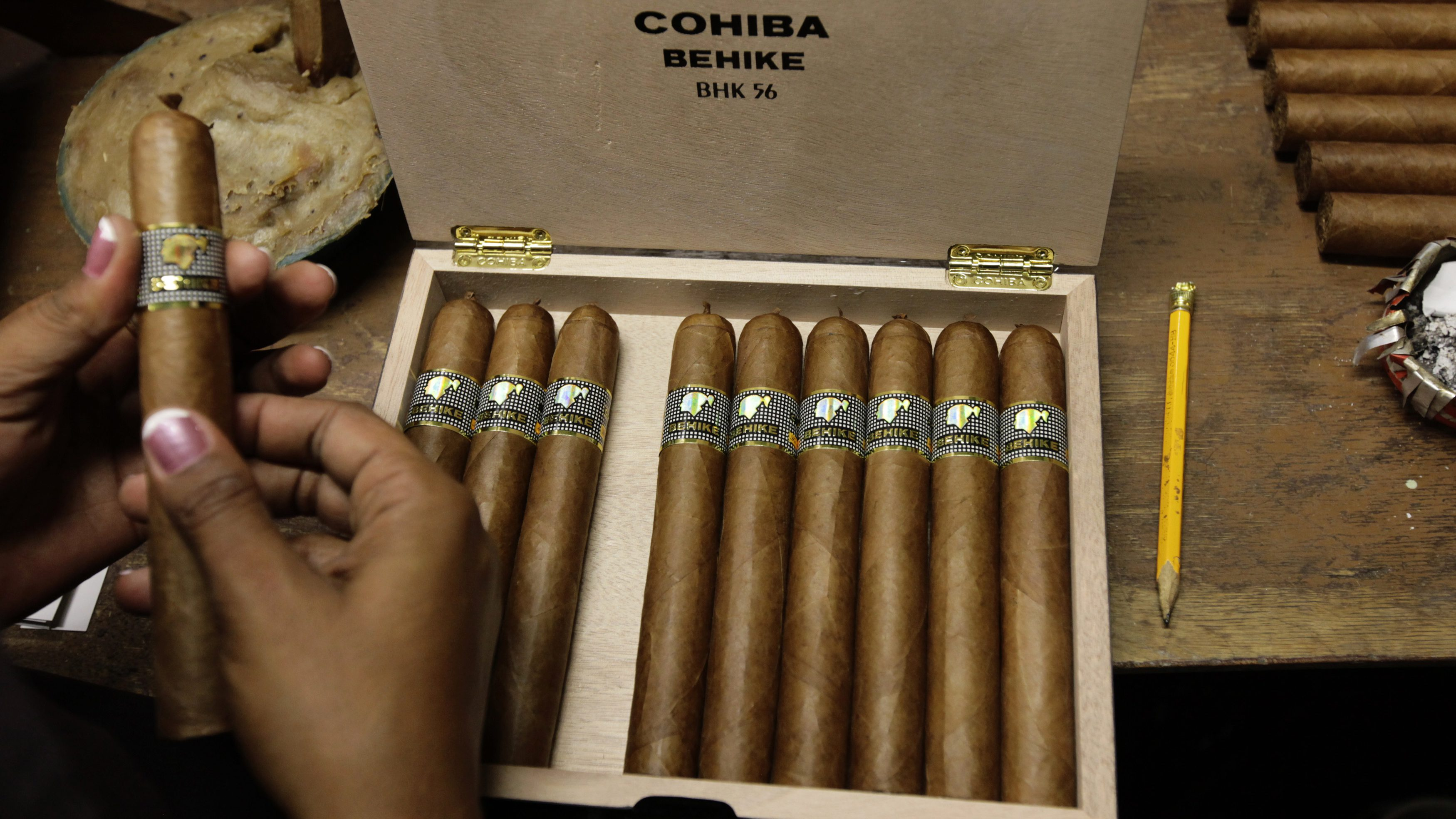 A woman fills a box of high end cigars at the Cohiba factory in Havana.