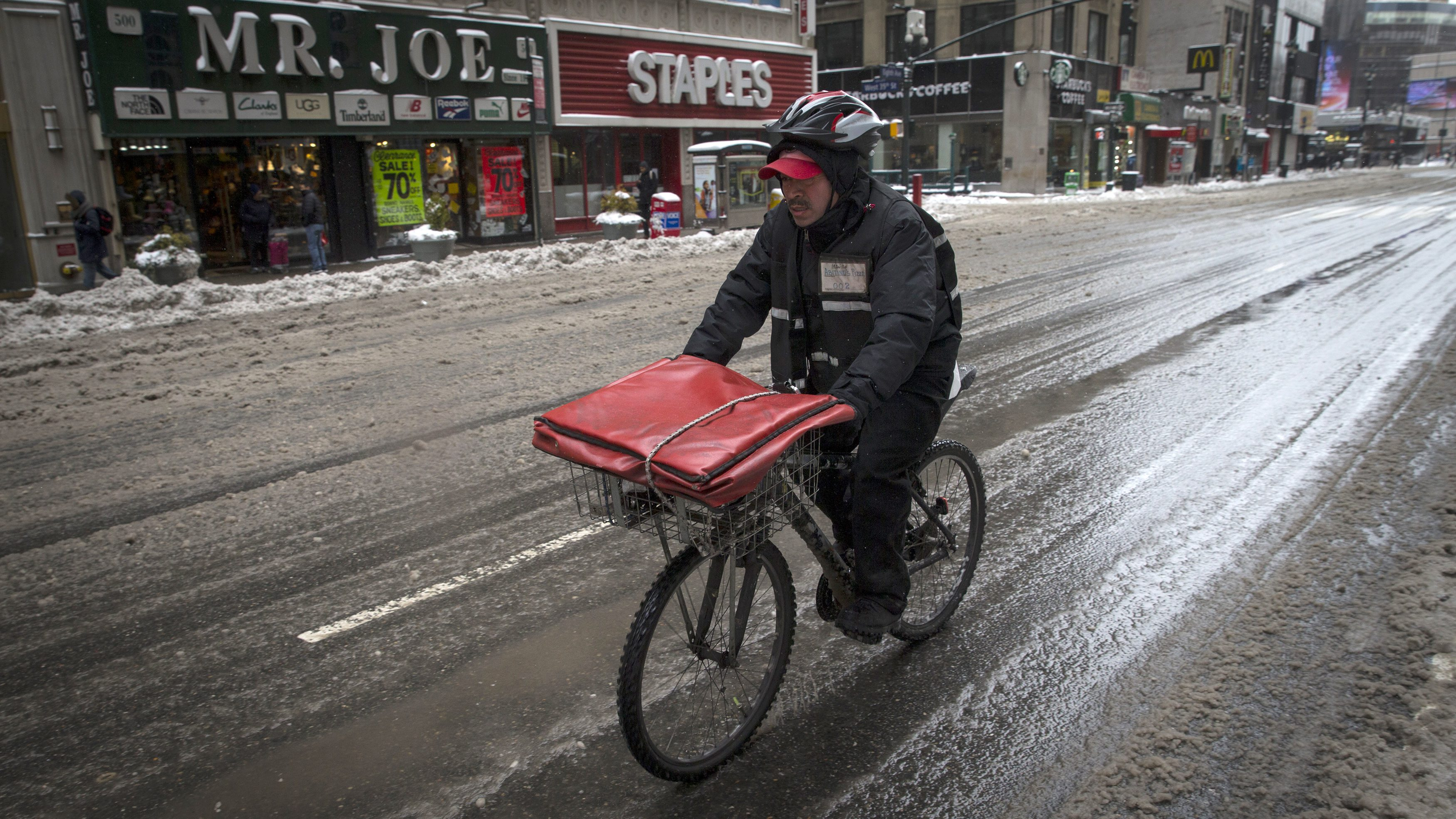 A pizza delivery man rides on a bicycle in New York.