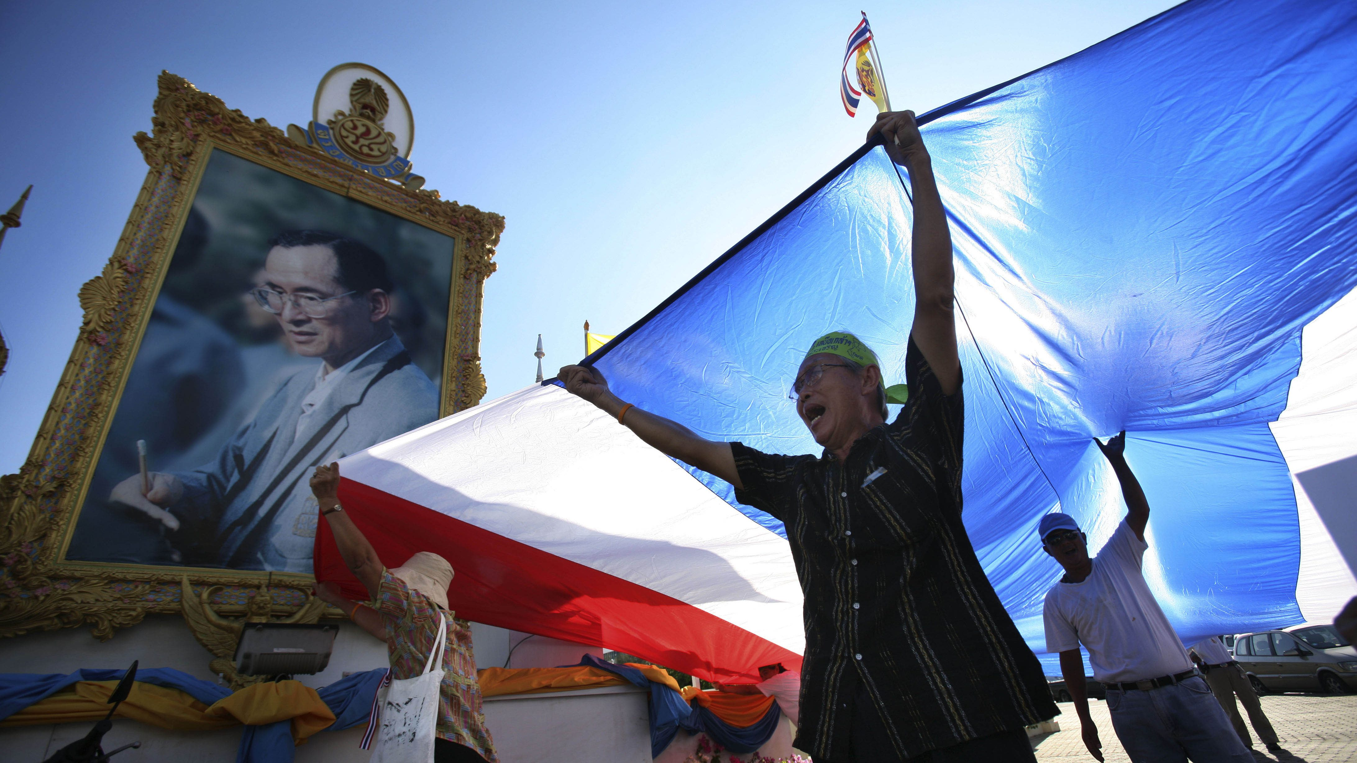 Pro-government supporters chant slogans with a Thai national flag in front of a portrait of King Bhumibol Adulyadej, Sunday, May 9, 2010 in Bangkok, Thailand. Prime Minister Abhisit Vejjajiva pleaded Sunday for an end to two months of street protests paralyzing part of the capital and an acceptance of his reconciliation plan that has been stalled by fresh violence. (AP Photo/Wally Santana)