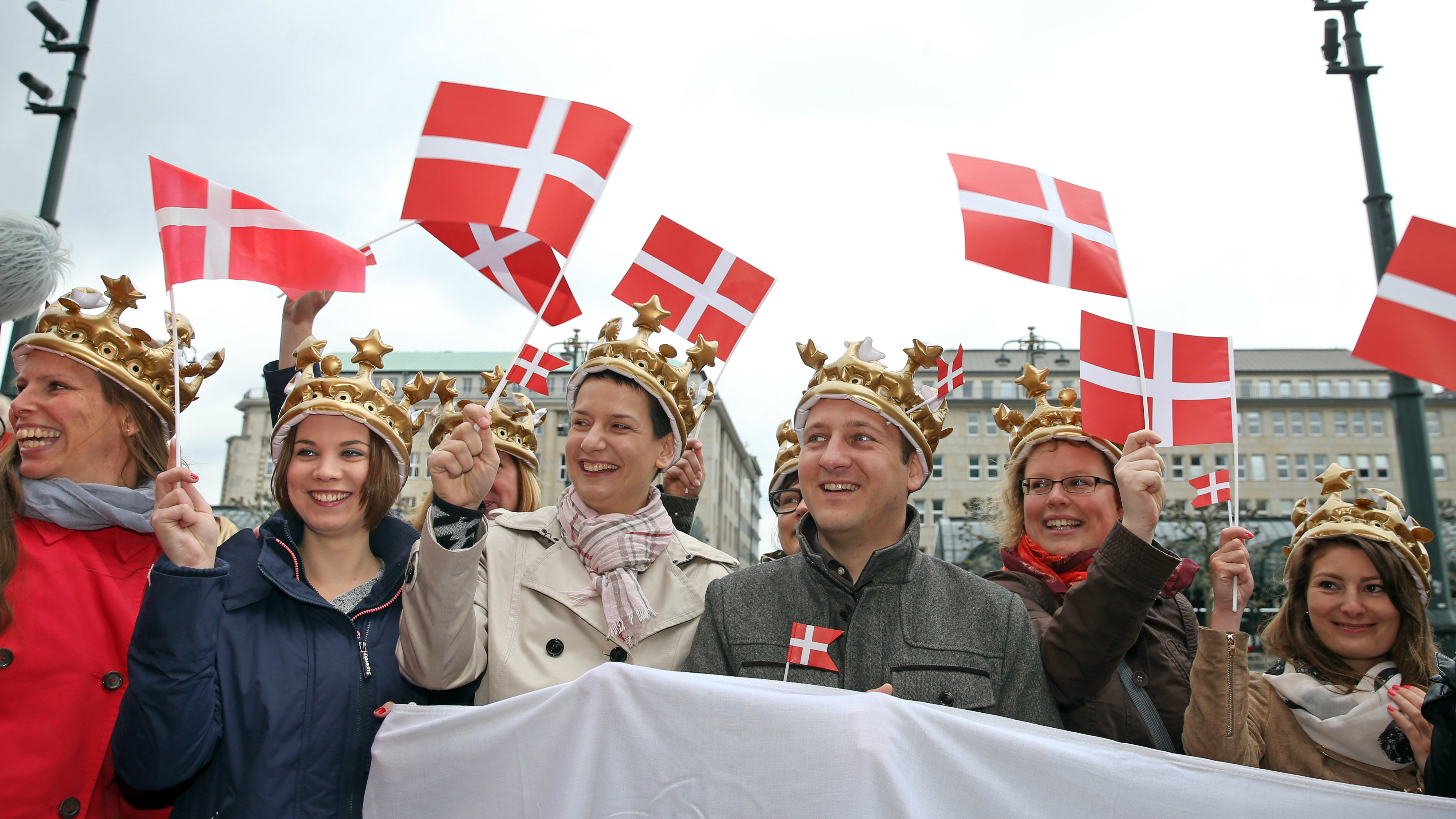 Fans of the Danish royal family carry Danish flags as they await the arrival of Danish Crown Prince and Princess