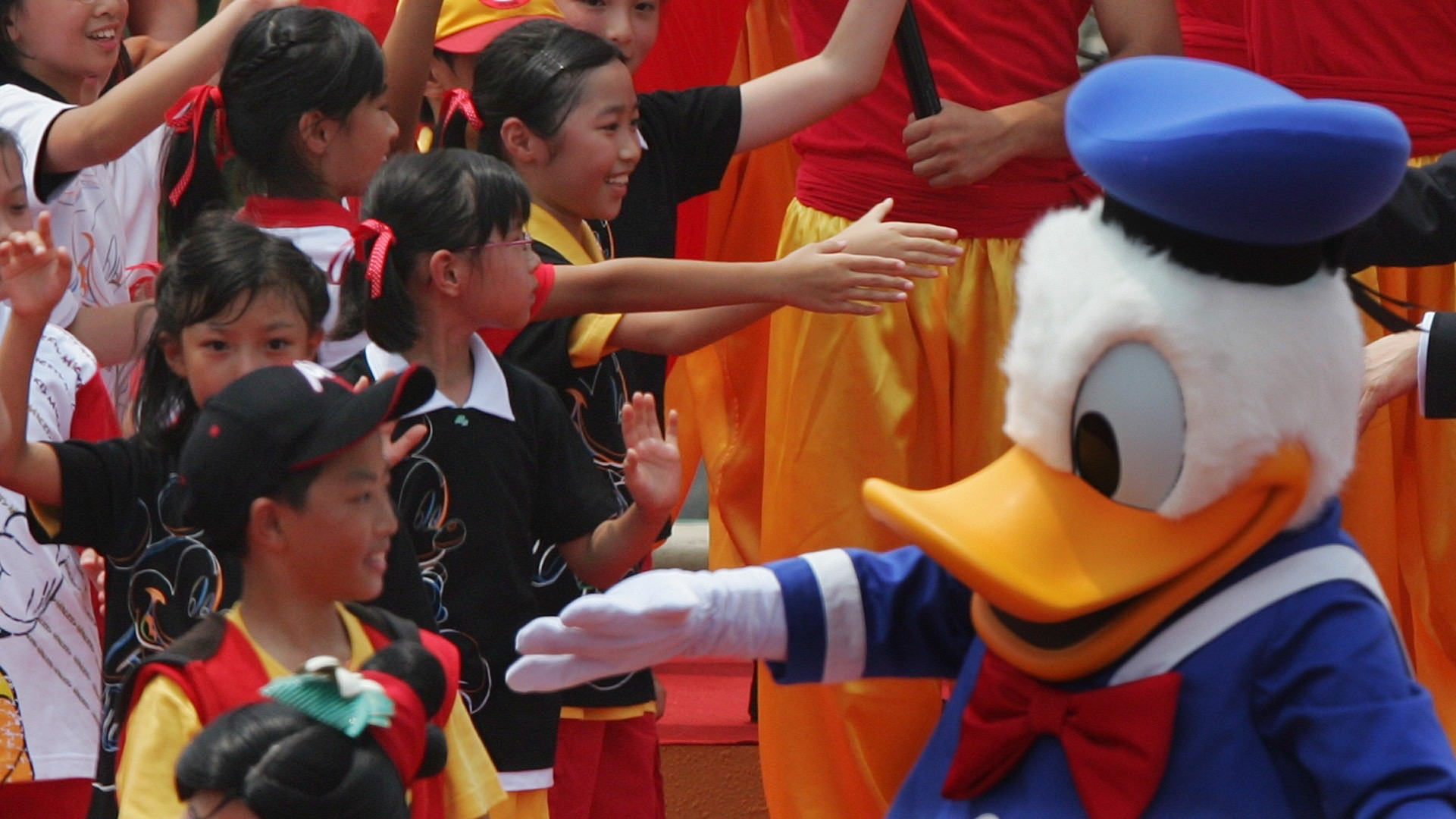 Hong Kong Chief Executive Donald Tsang (R) and Disney character Donald Duck greet young performers during the opening ceremony of Hong Kong Disneyland September 12, 2005. Disney officially opens its new Hong Kong theme park on Monday, bringing a slice of the Magic Kingdom to the Middle Kingdom with a careful blend of American showmanship and Chinese characteristics. REUTERS/Bobby Yip  BY/mk - RTRNLAU