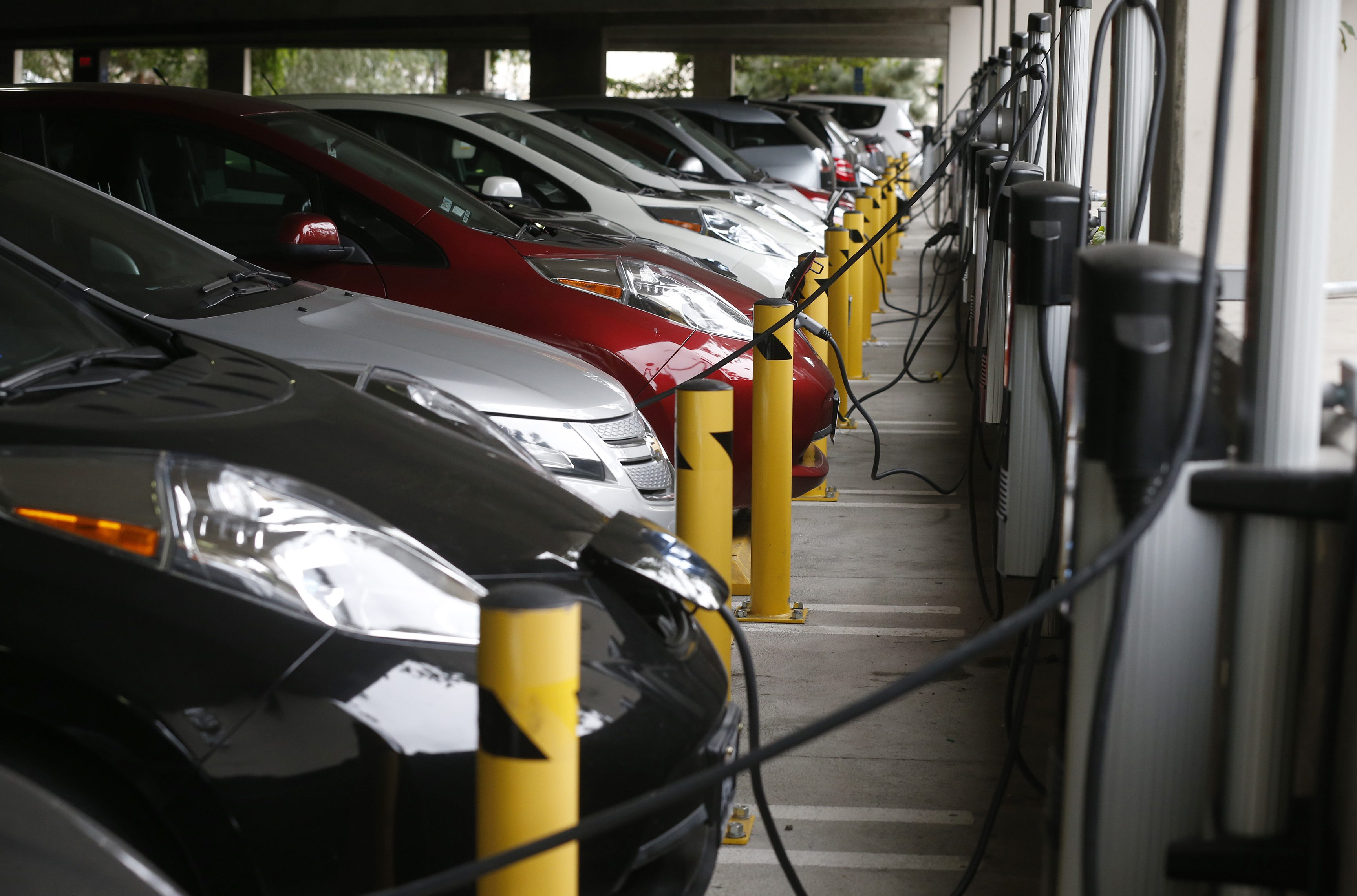 Electric cars sit charging in a parking garage at the University of California, Irvine January 26, 2015.