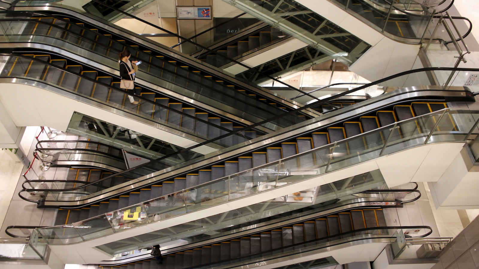 A woman rides an escalator at a shopping mall in Beijing, China, September 23, 2015. Rising vacancy rates and plummeting rents are increasingly common in Chinese malls and department stores, despite official data showing a sharp rebound in retail sales that helped the world's second-largest economy beat expectations in the third quarter. The answer to that apparent contradiction lies in the rising competition from online shopping and government purchases possibly boosting retail statistics. Add poorly managed properties into the equation and the empty malls aren't much of a surprise. Picture taken September 23, 2015. REUTERS/Kim Kyung-Hoon - RTX1T6UC