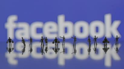 Photo illustration of 3D-printed models of people in front of a Facebook logo
