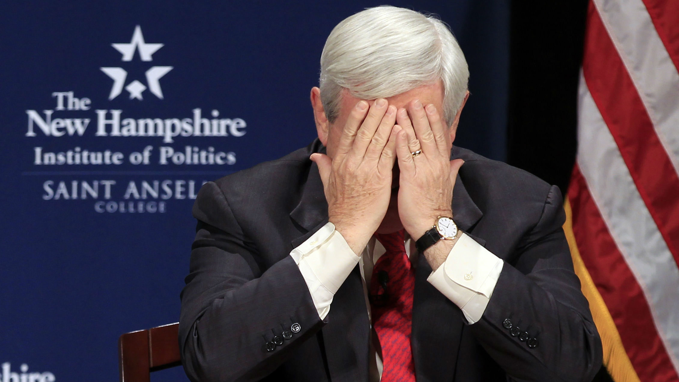 U.S. Republican presidential candidate former U.S. House Speaker Newt Gingrich covers his face with his hands during his Lincoln-Douglas style debate with fellow candidate and former Utah Governor Jon Huntsman at St. Anselm College in Manchester, New Hampshire December 12, 2011.