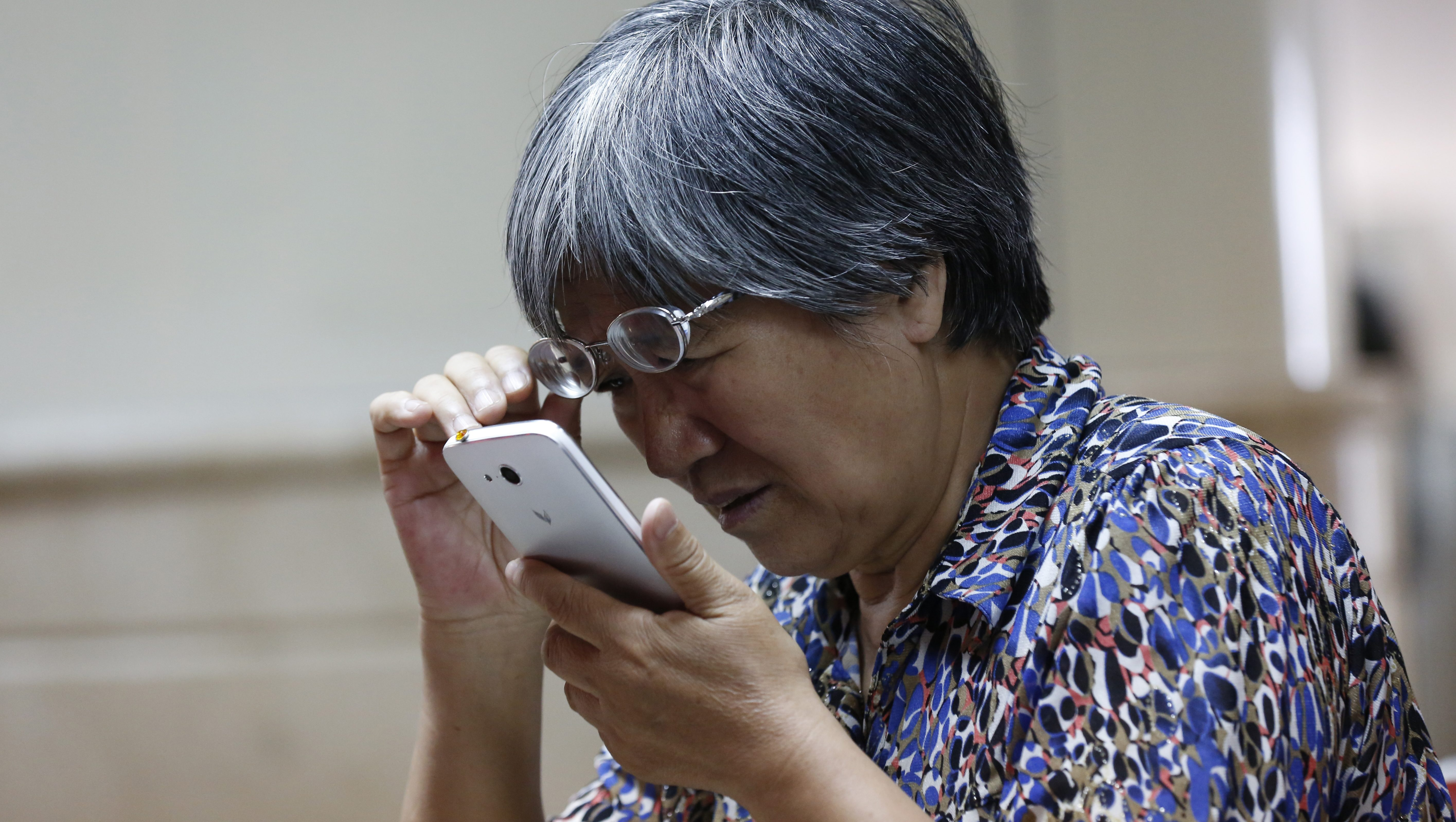 A stock investor checks the stock prices by a mobile phone at a brokerage house in Beijing city, China, 25 May 2015. China's shares climb to highest level in seven years that the benchmark Shanghai Composite Index rising 3.35 percent, or 156.2 points, to finish at 4,813.8 points and the Shenzhen Component Index gained 1.9 percent, or 305.26 points, to close at 16,351.06 points.