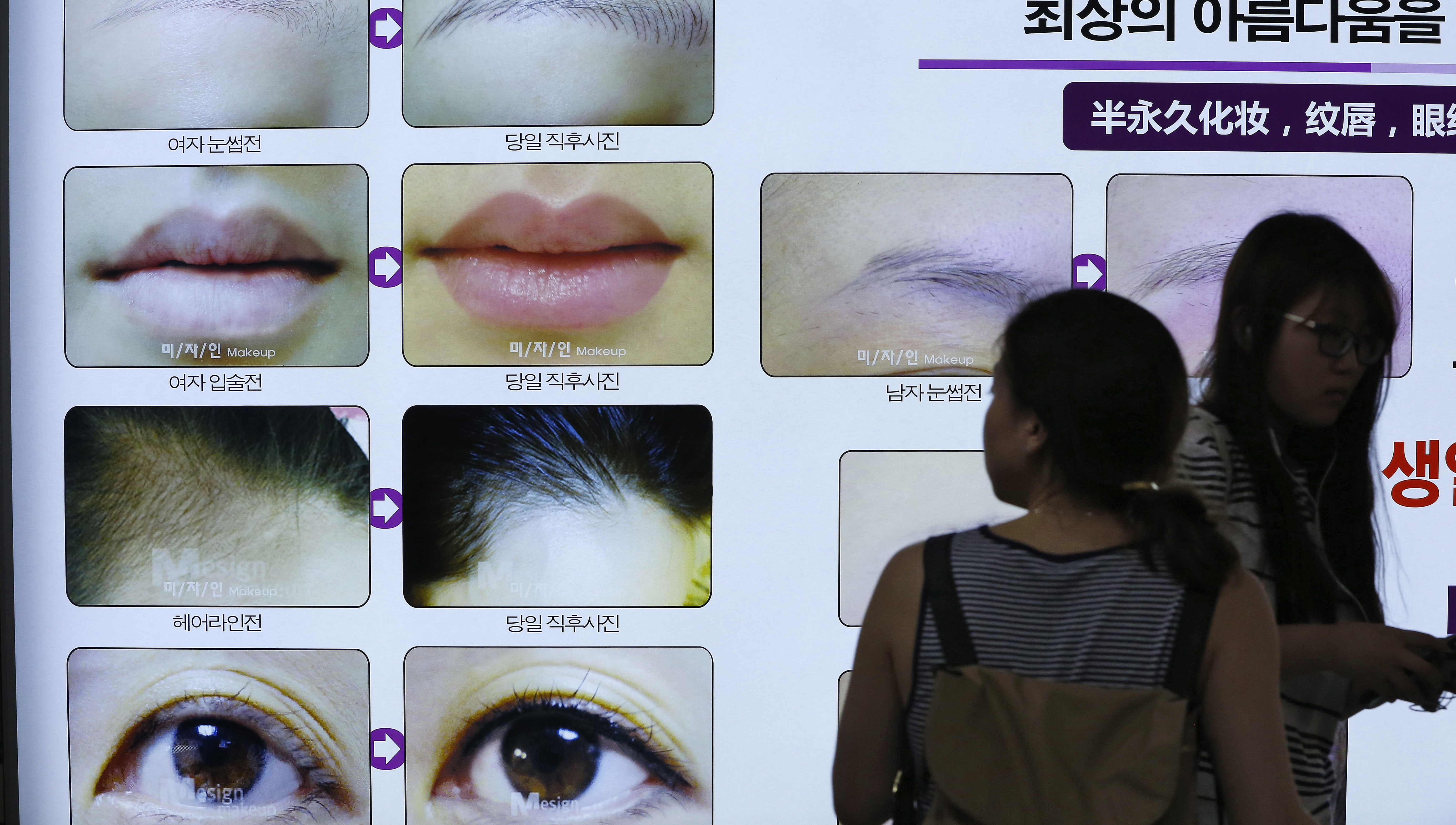 South Korean women pass by an advertising board for a plastic surgery clinic at the Apgujeong subway line 3 station south of Seoul, South Korea, 26 May 2015.