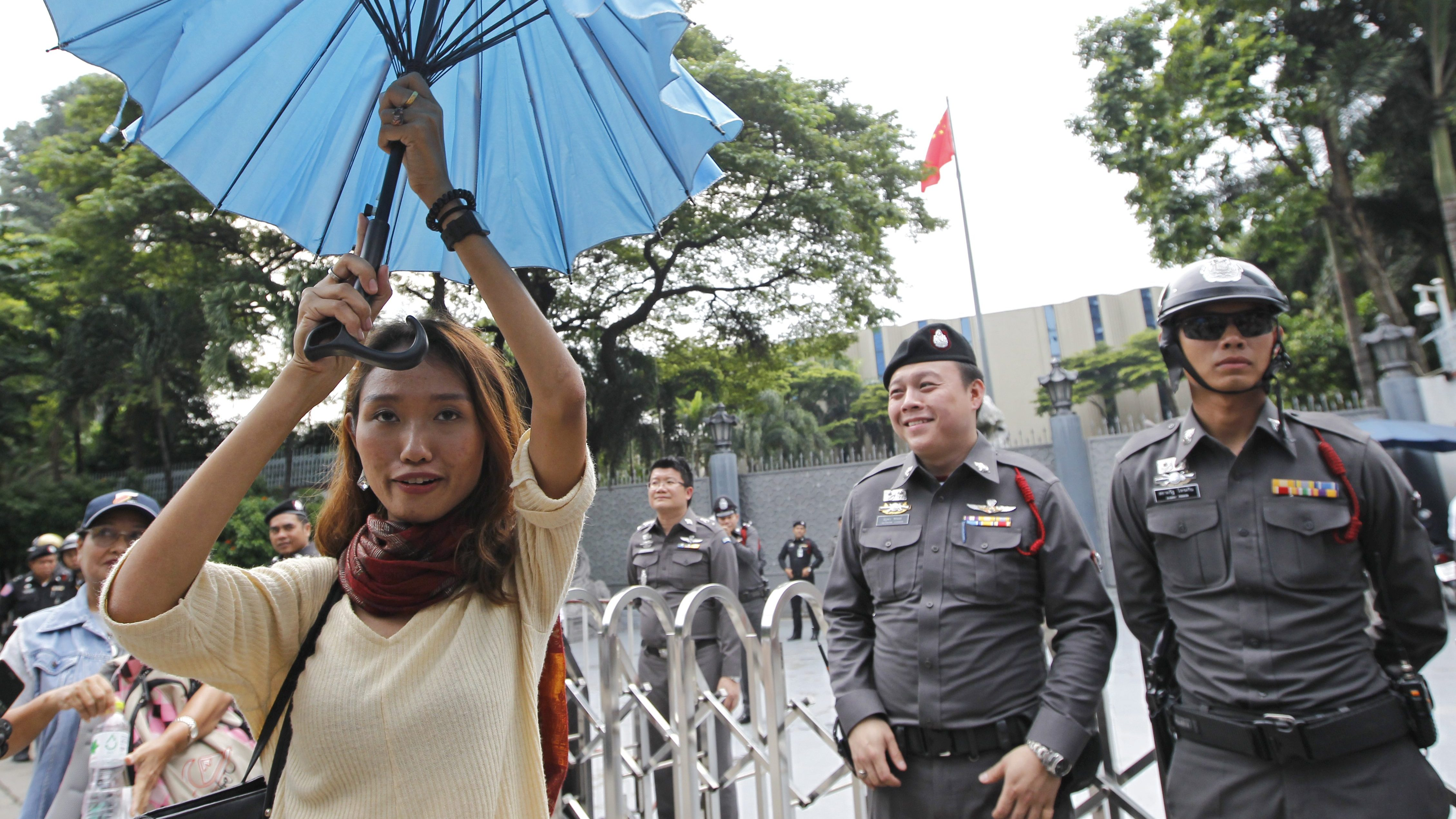 """A Thai pro-democracy activist holds an umbrella as a symbol of Hong Kong's """"Umbrella Movement"""" after Hong Kong democracy activist Joshua Wong was deported from Bangkok airport, in front of the Chinese embassy in Bangkok, Thailand, 5 October 2016."""