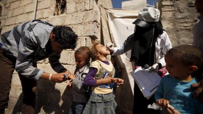 Health workers administer polio vaccine for children during a house-to-house vaccination campaign in Yemen's capital Sanaa