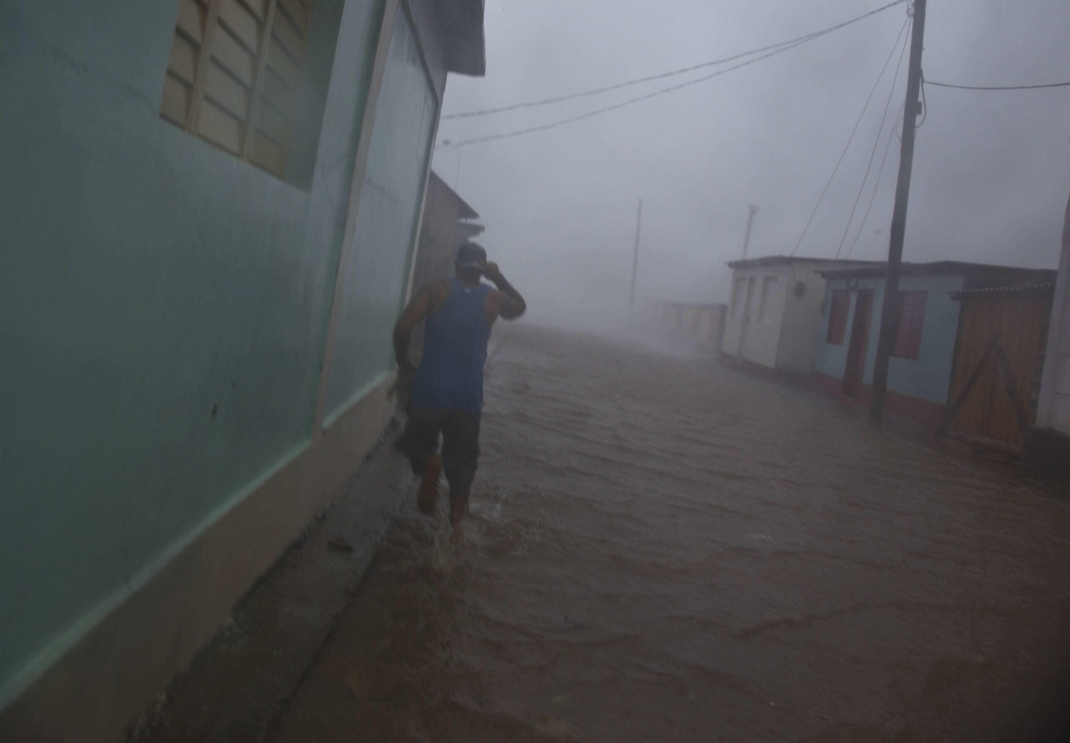 A resident runs in a flooded street as Hurricane Matthew roars over Baracoa, Cuba on Oct. 4, 2016.