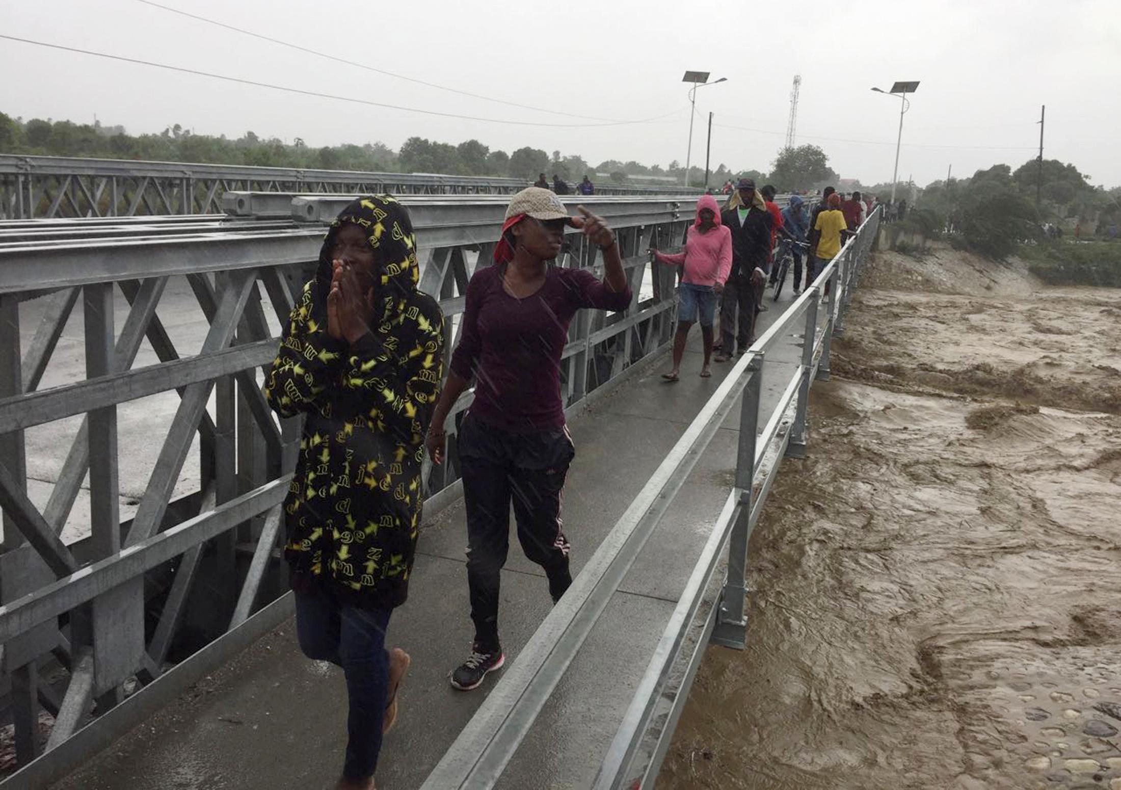 People cross a bridge while Hurricane Matthew passes in Port-au-Prince
