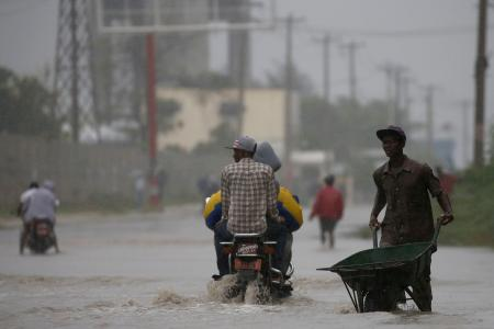 People wade across a flooded street while Hurricane Matthew passes through Port-au-Prince on Oct. 4.