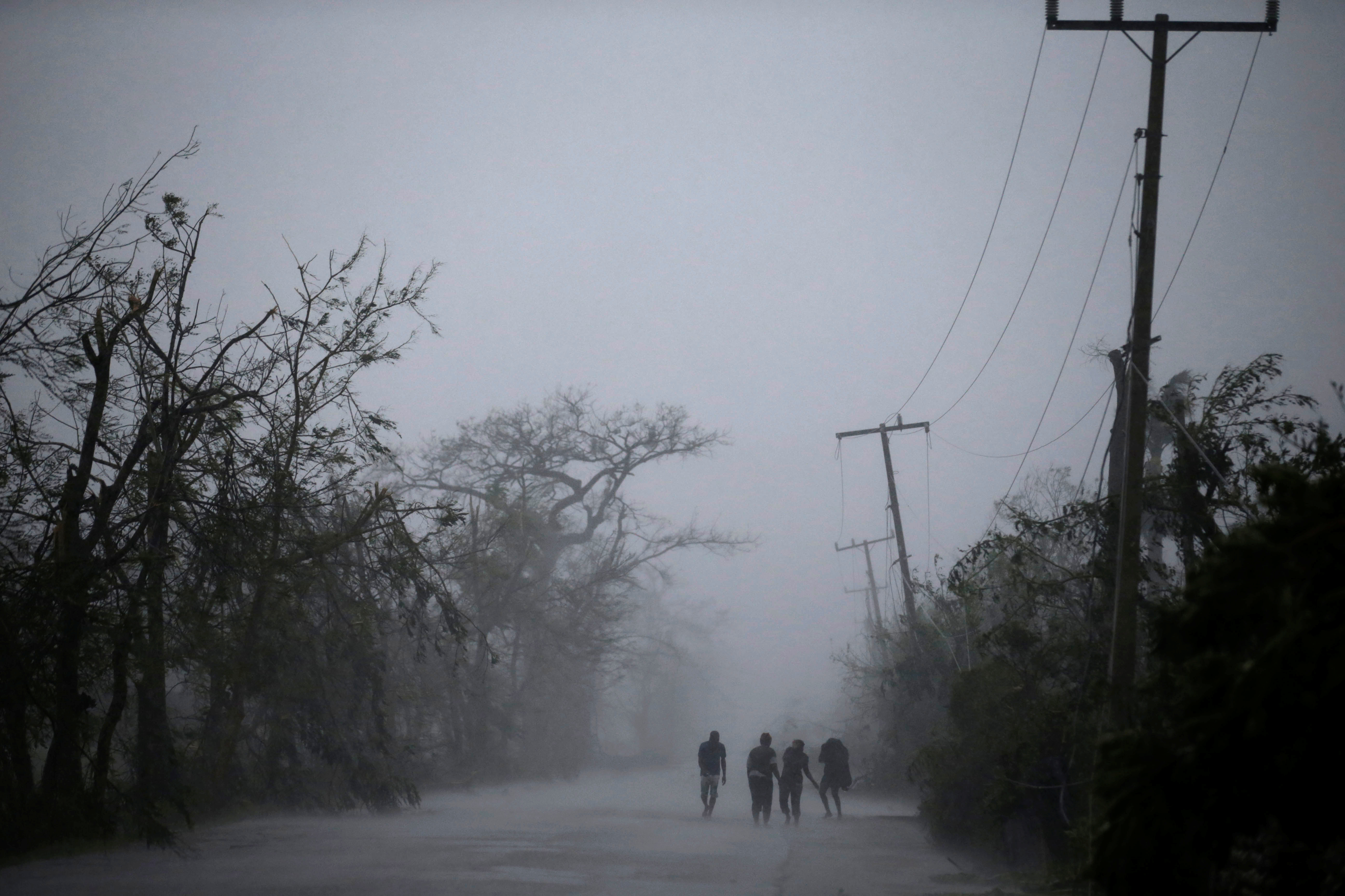 People walk on the road as rain falls during Hurricane Matthew in Les Cayes, Haiti on Oct. 4.