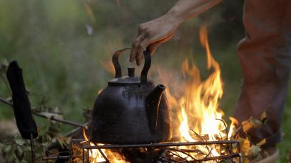 A volunteer takes a kettle from a bonfire near the remote village of Budy