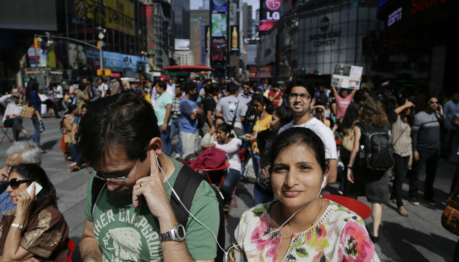 A couple shares a set of headphones as they gather in Times Square with other members of the Indian-American community to watch a live stream of Indian Prime Minister Narendra Modi speaking to a capacity crowd at Madison Square Garden, Sunday, Sept. 28, 2014, in New York. A day after addressing a hushed U.N. General Assembly, where headphone-wearing delegates rarely break into a smile, India's new prime minister told a packed and boisterous crowd to help him develop his nation's economy, vowing that under his leadership, India won't look back.