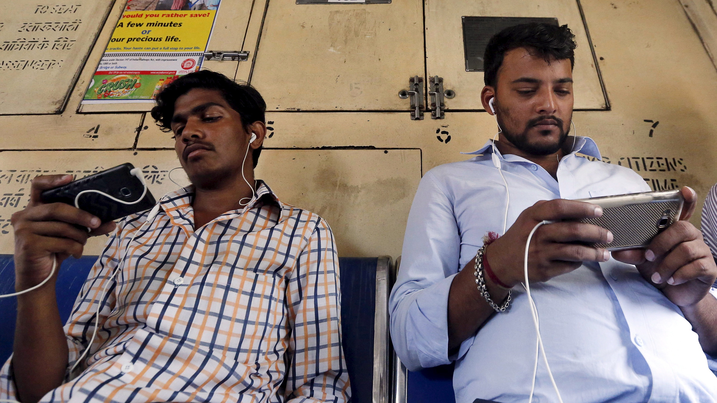 Commuters watch videos on their mobile phones as they travel in a suburban train in Mumbai, India, April 2, 2016. With smartphone sales booming and India preparing for nationwide 4G Internet access, India's film and TV industry hopes the ease of tapping your phone for the latest release will generate profits at last, overcoming the problems of woefully few cinemas and rampant piracy. Picture taken April 2, 2016.