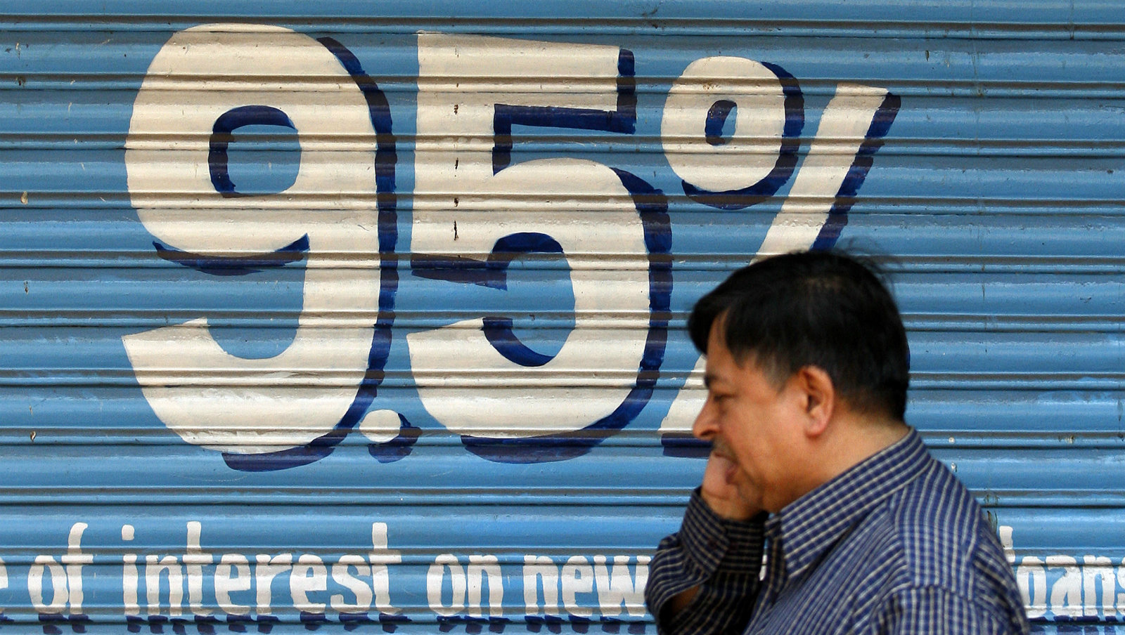 A man walks past a bank advertisement for four wheeler vehicle loans in Mumbai March 22, 2010. The Reserve Bank of India (RBI) on Friday unexpectedly raised interest rates from record-low levels for the first time since it began cutting in 2008, citing intensifying inflationary pressures and a steady economic recovery.