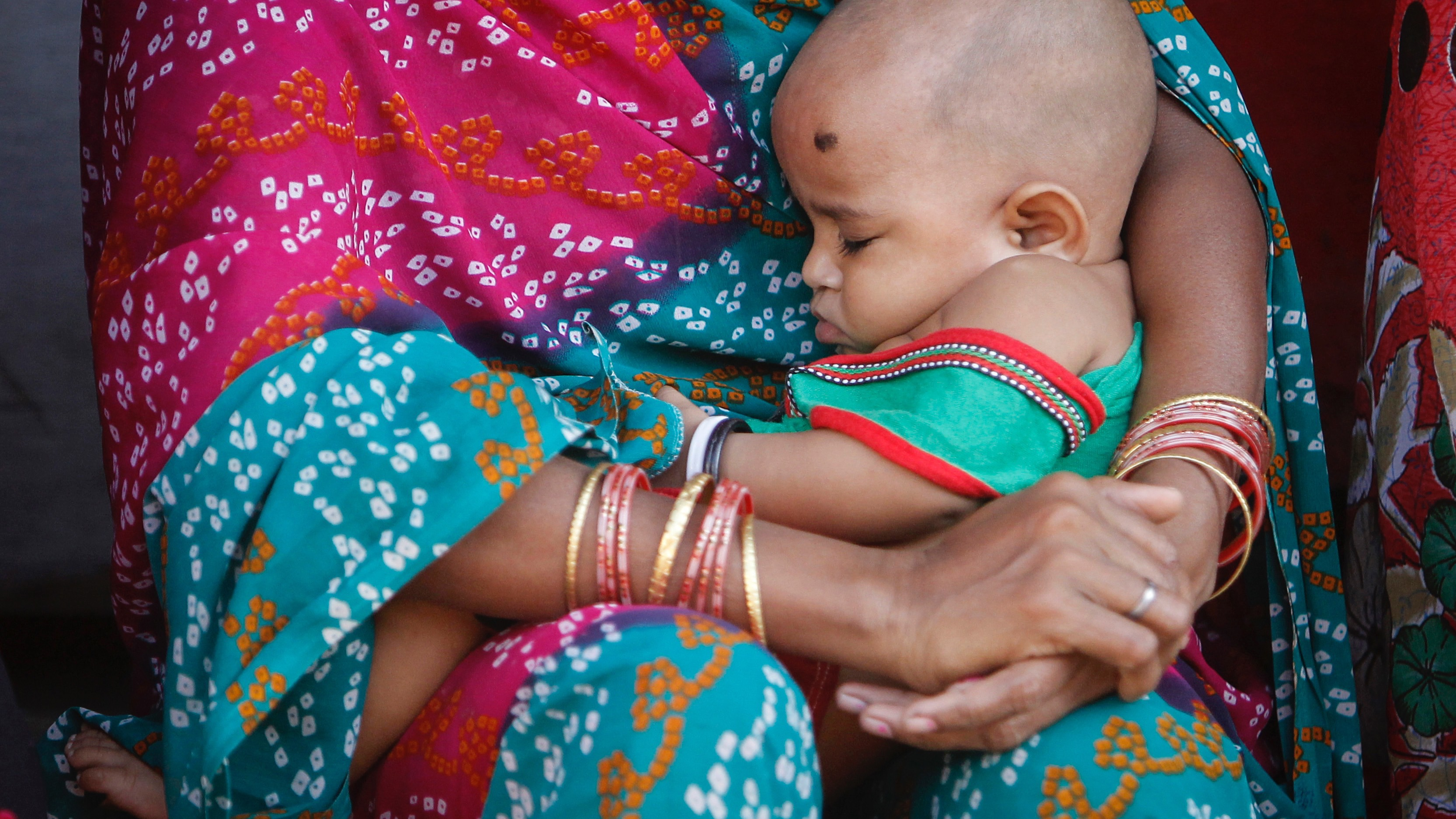 A woman holding her baby sits in a street at a slum in Mumbai January 28, 2014. REUTERS/Danish Siddiqui (INDIA - Tags: SOCIETY) - RTX17YIL