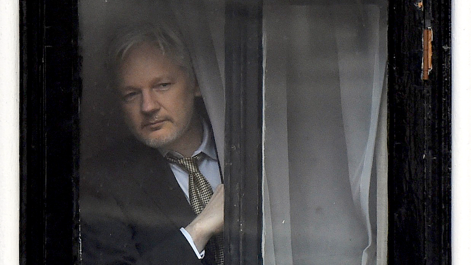 WikiLeaks founder Julian Assange peers out from behind a curtain before emerging to make a speech from the balcony of the Ecuadorian Embassy, in central London, Britain February 5, 2016. Assange should be allowed to go free from the Ecuadorian embassy in London and be awarded compensation for what amounts to a three-and-a-half-year arbitrary detention, a U.N. panel ruled on Friday. REUTERS/Toby Melville - RTX25ML6