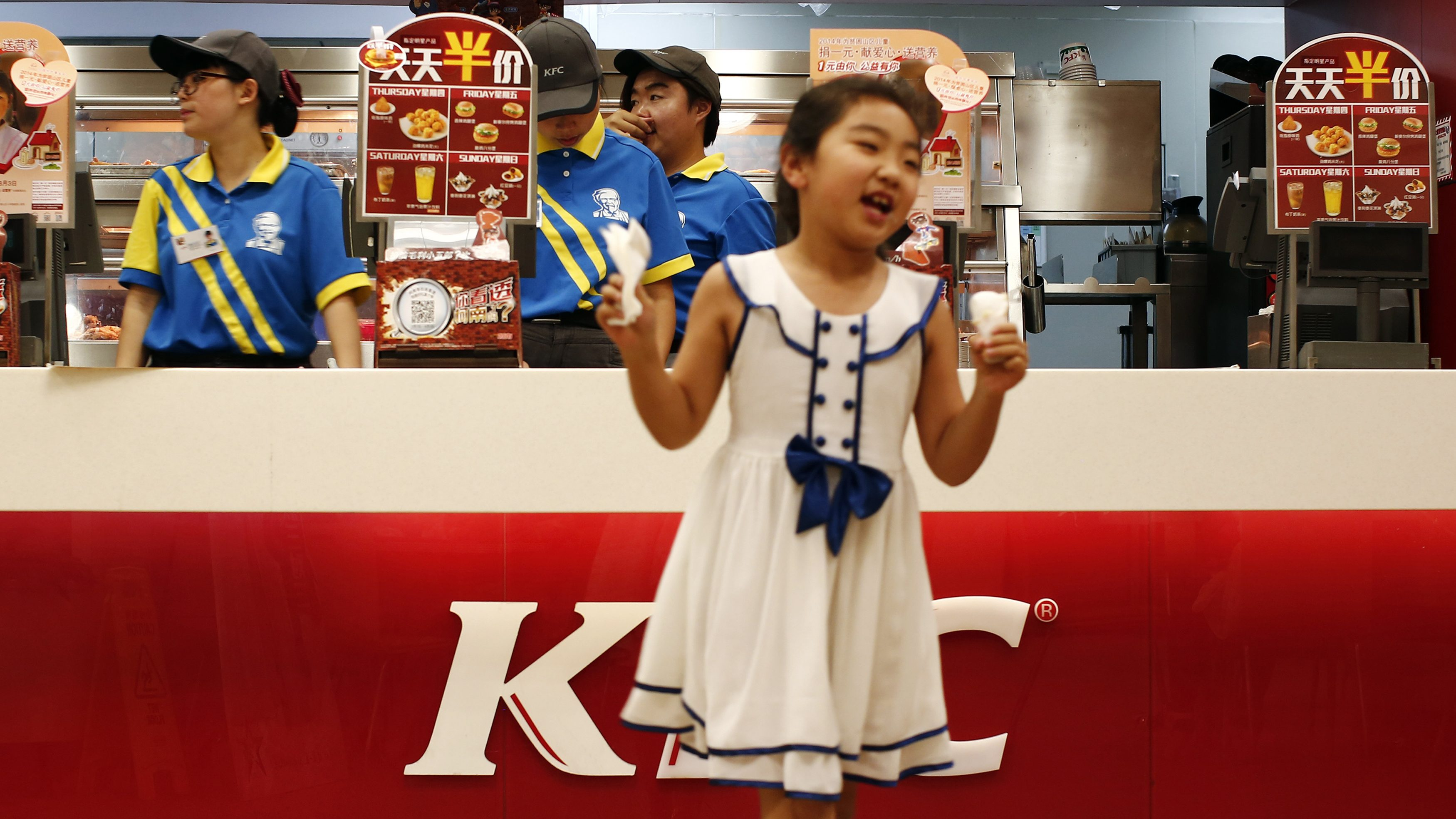 A girl reacts after buying ice cream at a KFC restaurant in Beijing July 17, 2014. Yum Brands Inc on Wednesday said its KFC business bounced back in China, its No. 1 market, but its stock fell more than 2 percent in extended-hours trading on disappointing quarterly results from its India, Taco Bell and Pizza Hut divisions.