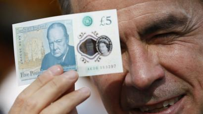 Mark Carney holds up a new £5 polymer note