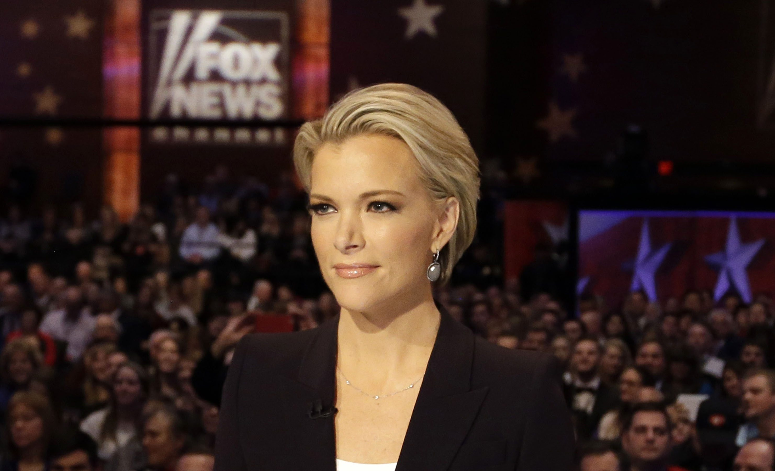 """FILE - In this Jan. 28, 2016 photo, Moderator Megyn Kelly waits for the start of the Republican presidential primary debate in Des Moines, Iowa.  Donald Trump says people who are bullied """"gotta get over it"""" and fight back. It's a message he delivers to Megyn Kelly, the Fox News anchor who sat down with him for an interview months after he savaged her on Twitter and elsewhere.  (AP Photo/Chris Carlson)"""