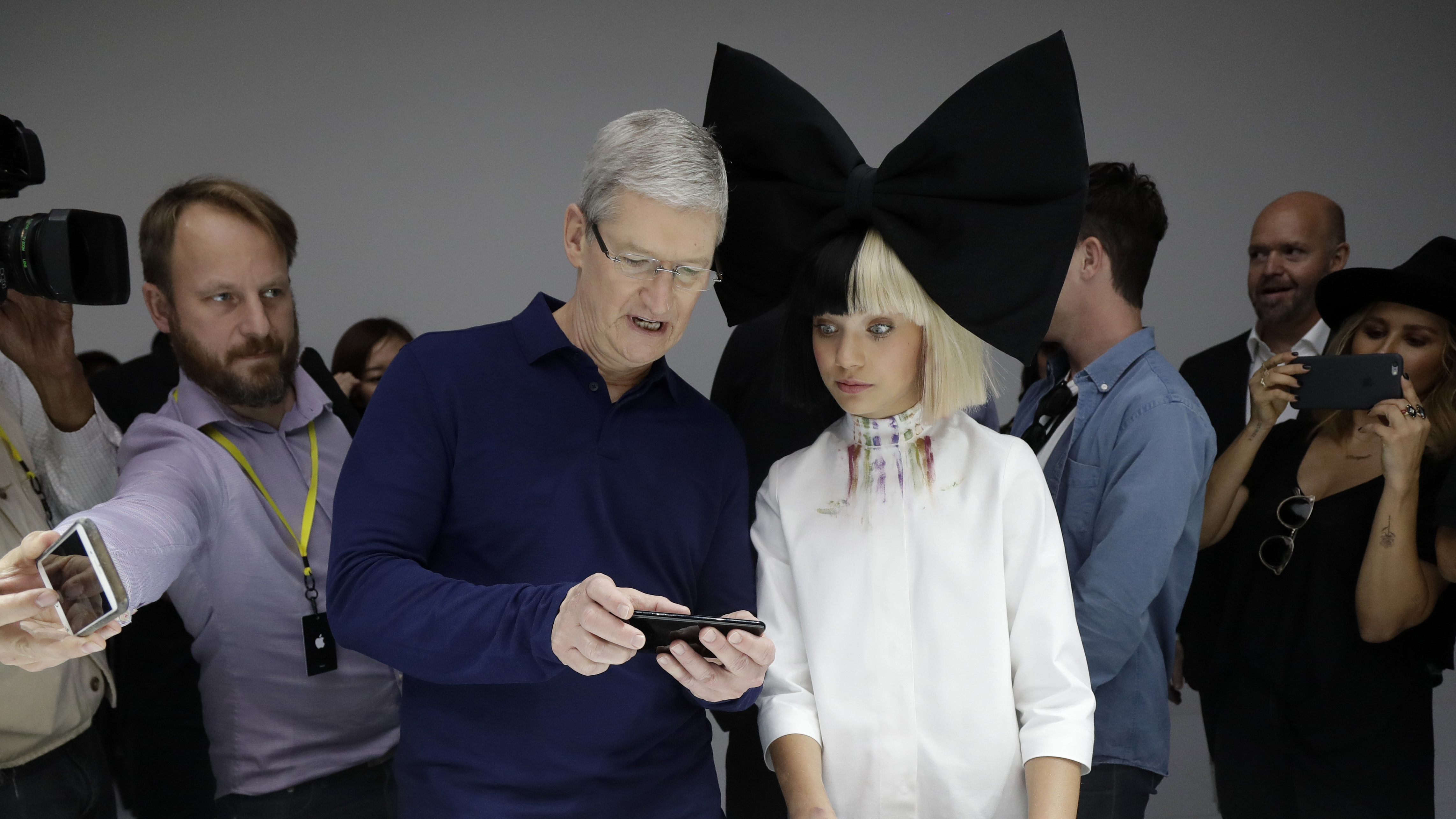 Apple CEO Tim Cook shows an iPhone 7 to performer Maddie Ziegler during an event to announce new products, Wednesday, Sept. 7, 2016, in San Francisco. (AP Photo/Marcio Jose Sanchez)