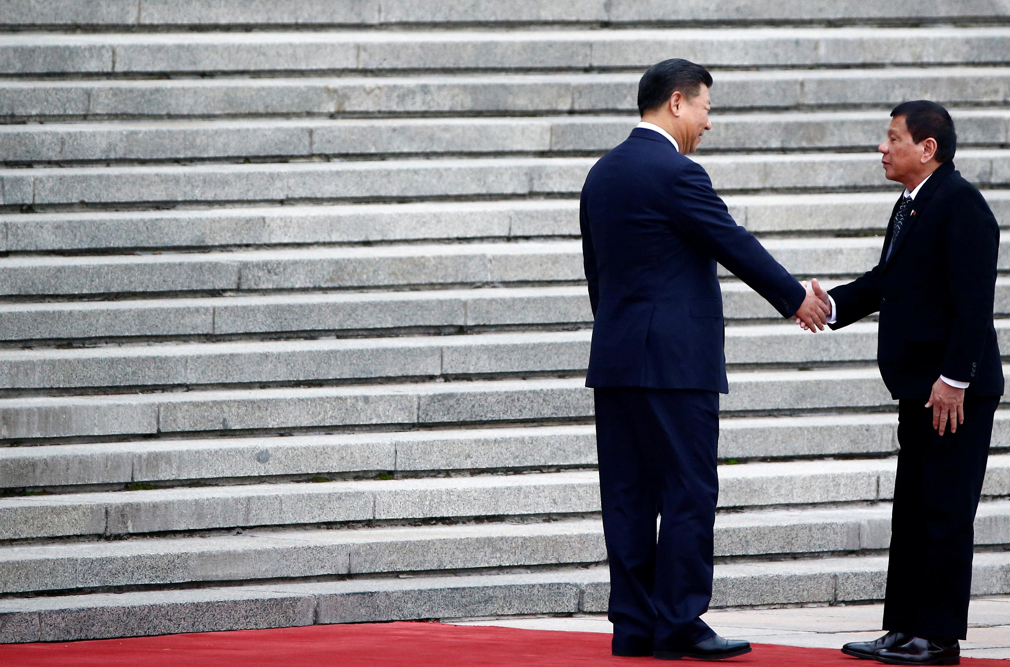 Philippines President Rodrigo Duterte and Chinese President Xi Jinping shake hands in Beijing.