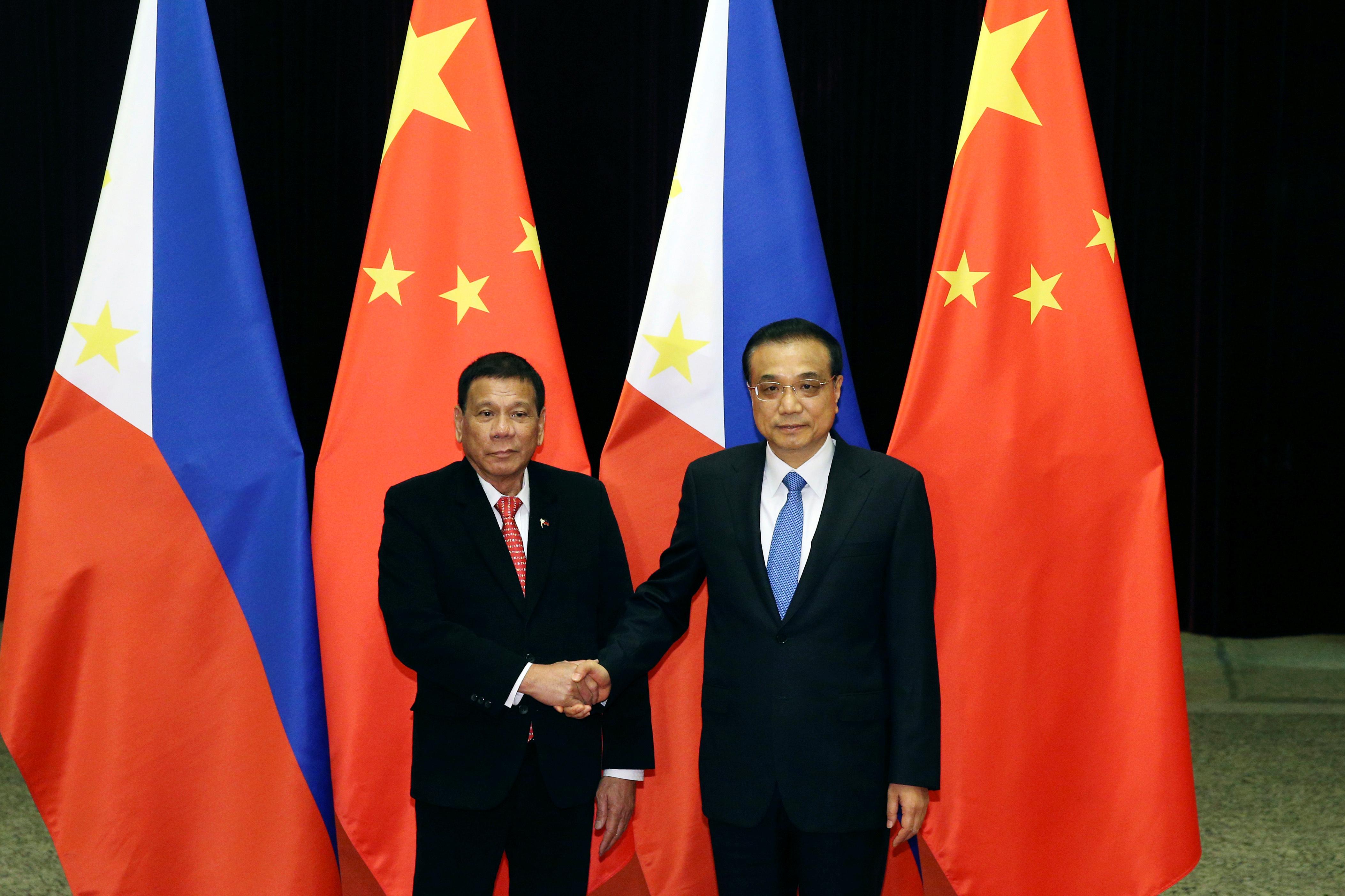 Philippines President Rodrigo Duterte shakes hands with Chinese Premier Li Keqiang.