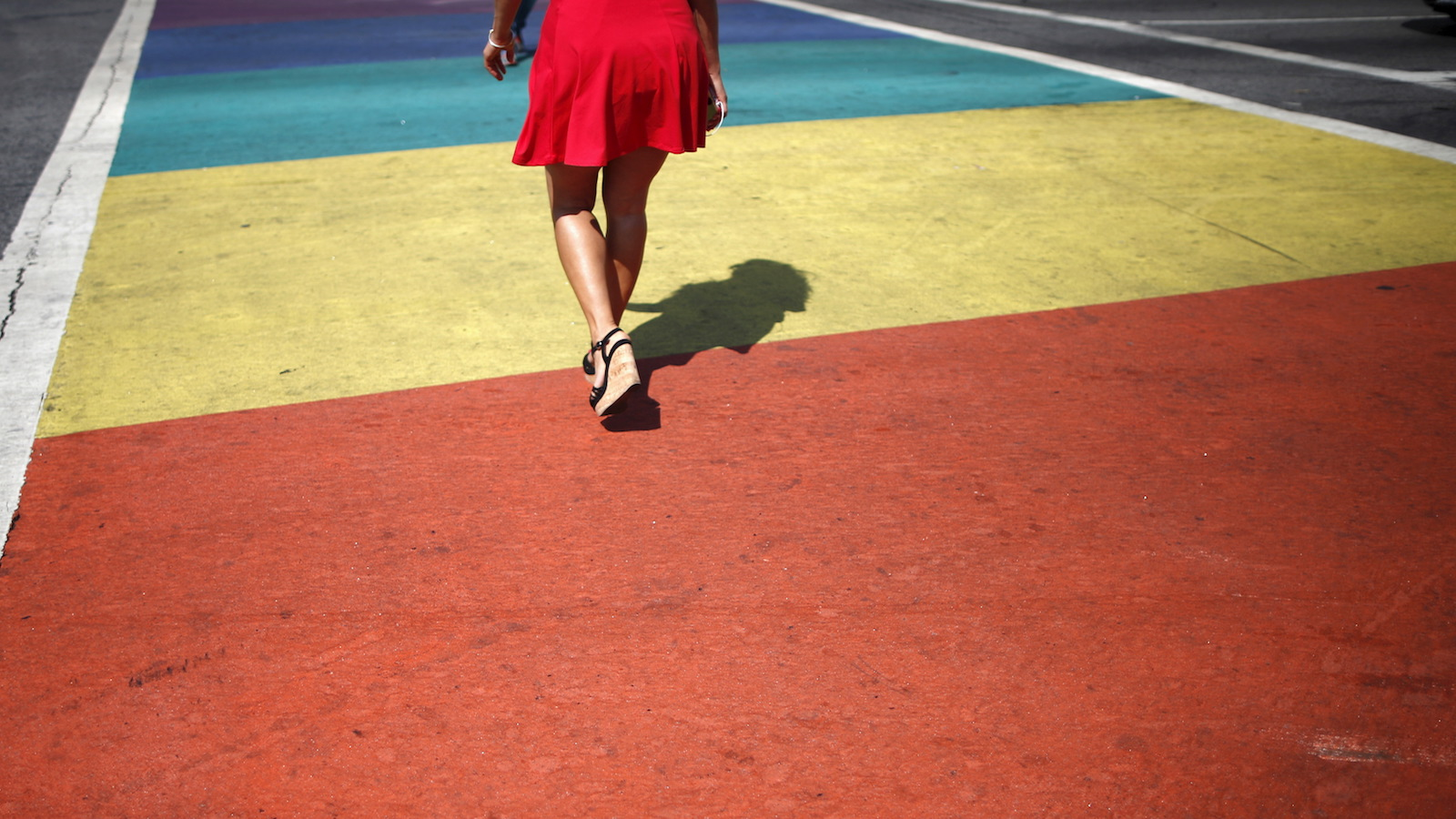 A person walks across a rainbow pedestrian crossing on a road in West Hollywood, United States, June 26, 2015. The U.S. Supreme Court ruled on Friday that the U.S. Constitution provides same-sex couples the right to marry in a historic triumph for the American gay rights movement. REUTERS/Lucy Nicholson       TPX IMAGES OF THE DAY      - RTX1HYR5