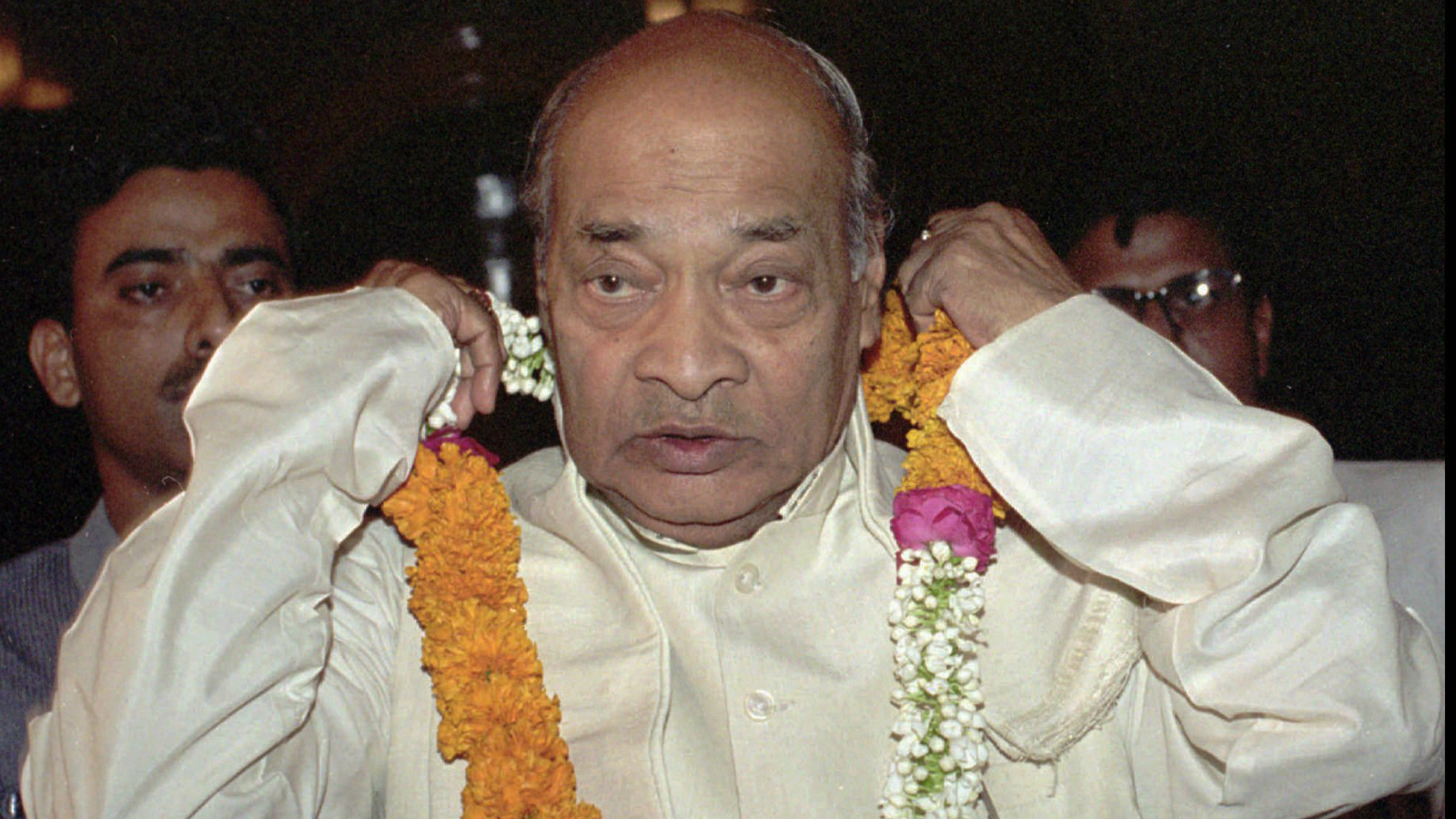 Indian Prime Minister P.V. Narasimha Rao removes a garland of flowers after arriving at parliament where the Congress Party re-elected him party president in New Delhi Sunday, May 12, 1996. Rao resigned as prime minister Friday following his Congress Party's election defeat but will continue as caretaker prime minister until a new government is formed.