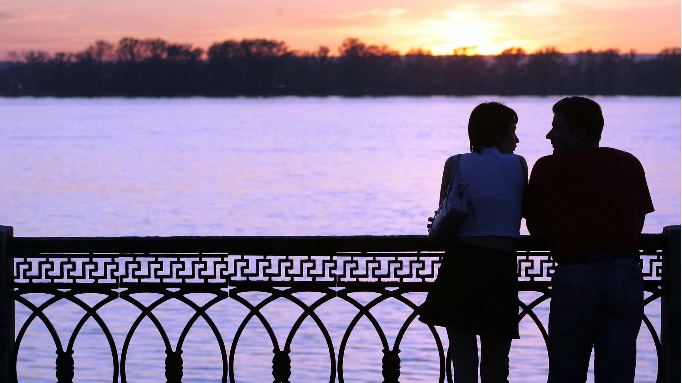 A couple stands close to one another on a bridge at sunset.