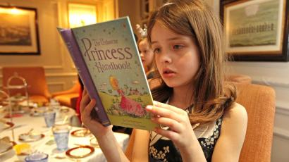 A young white girl reads a book