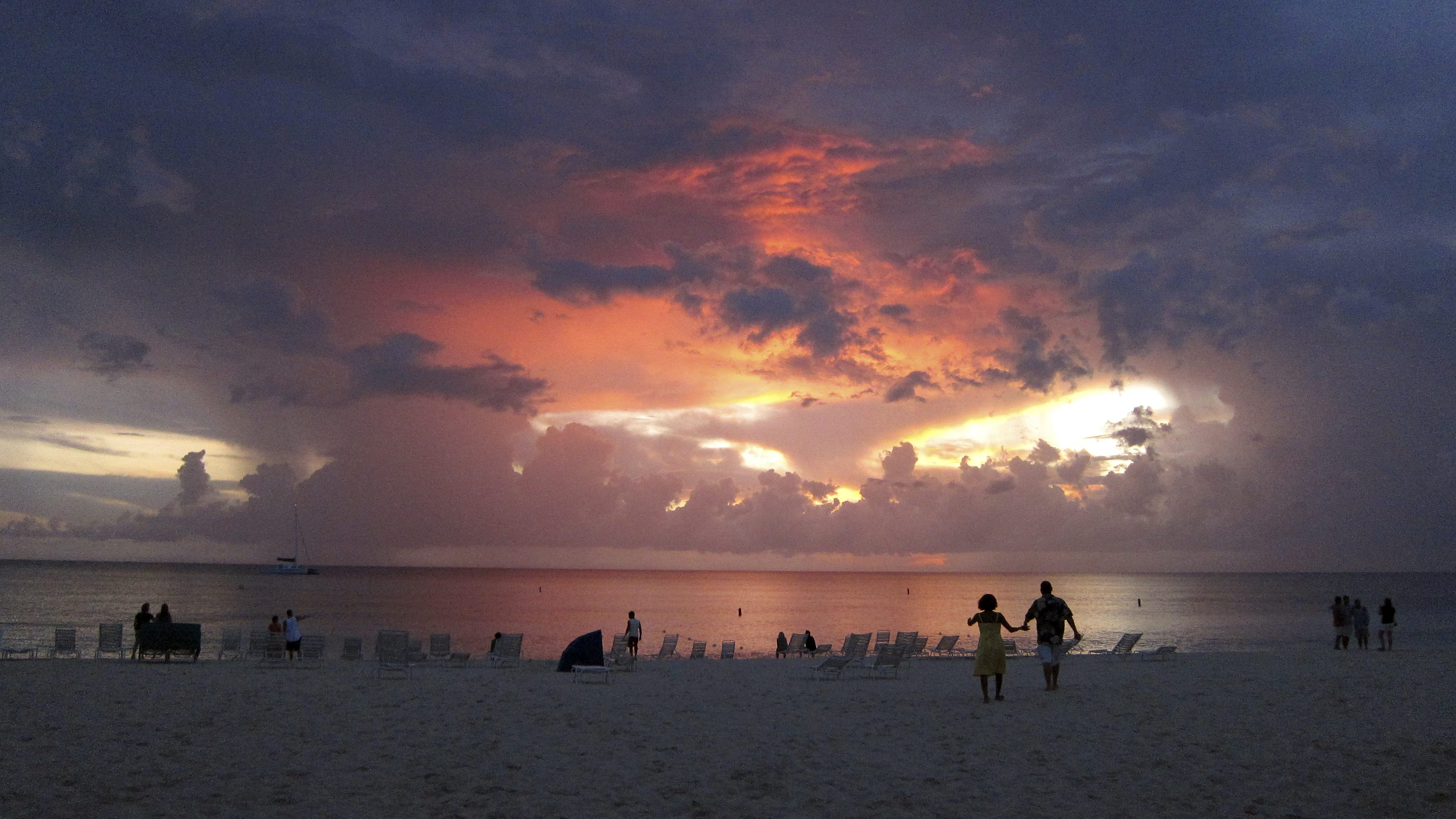 Tourists walk on Seven Mile Beach at sunset in George Town, Cayman Islands July 28, 2011. Cayman Islands, a tax haven, is the world's fifth-largest financial centre and hosts almost two-thirds of the world's hedge funds.