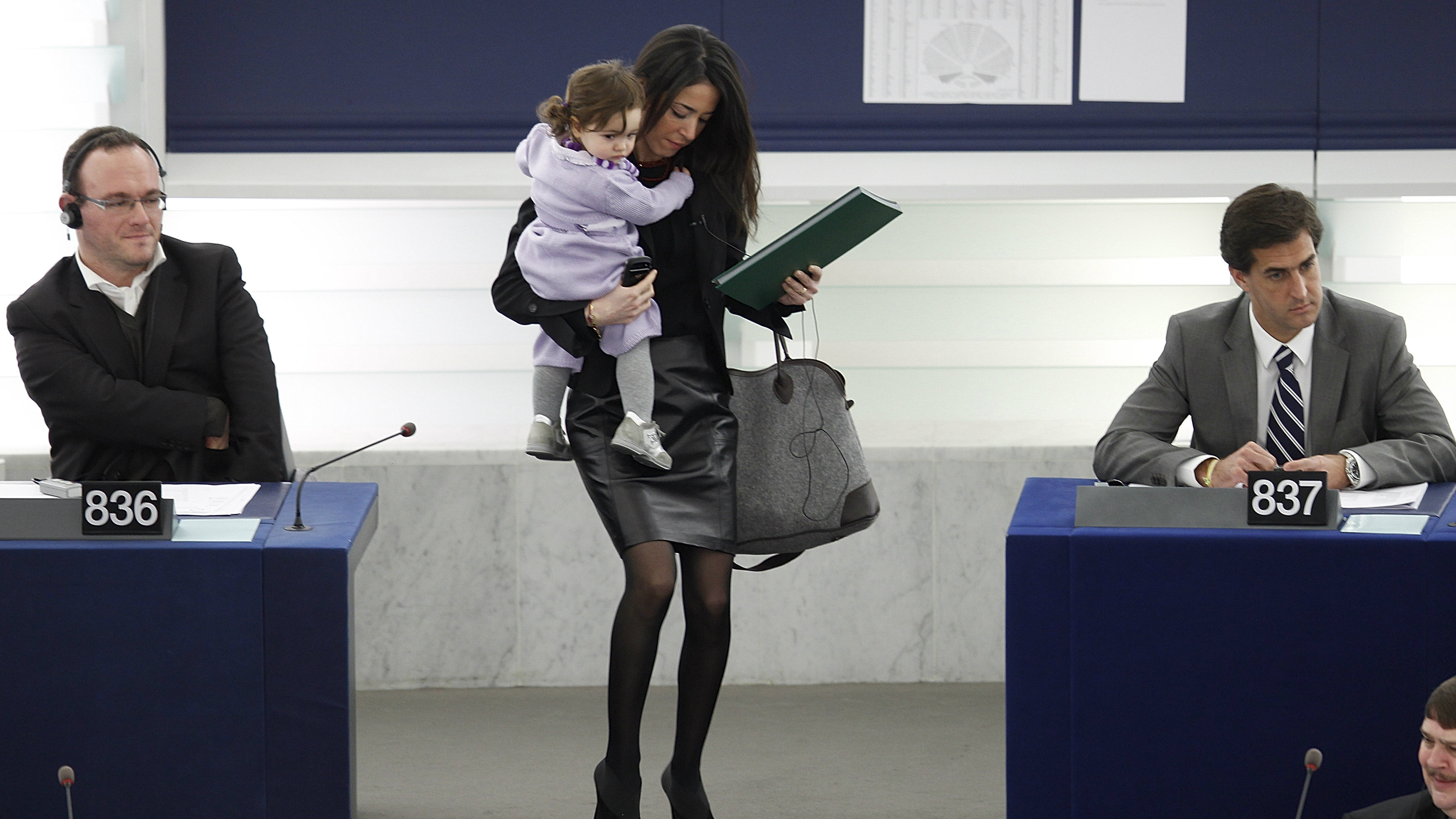 Italian Member of the European Parliament Ronzulli juggling her child, a bag and a folder